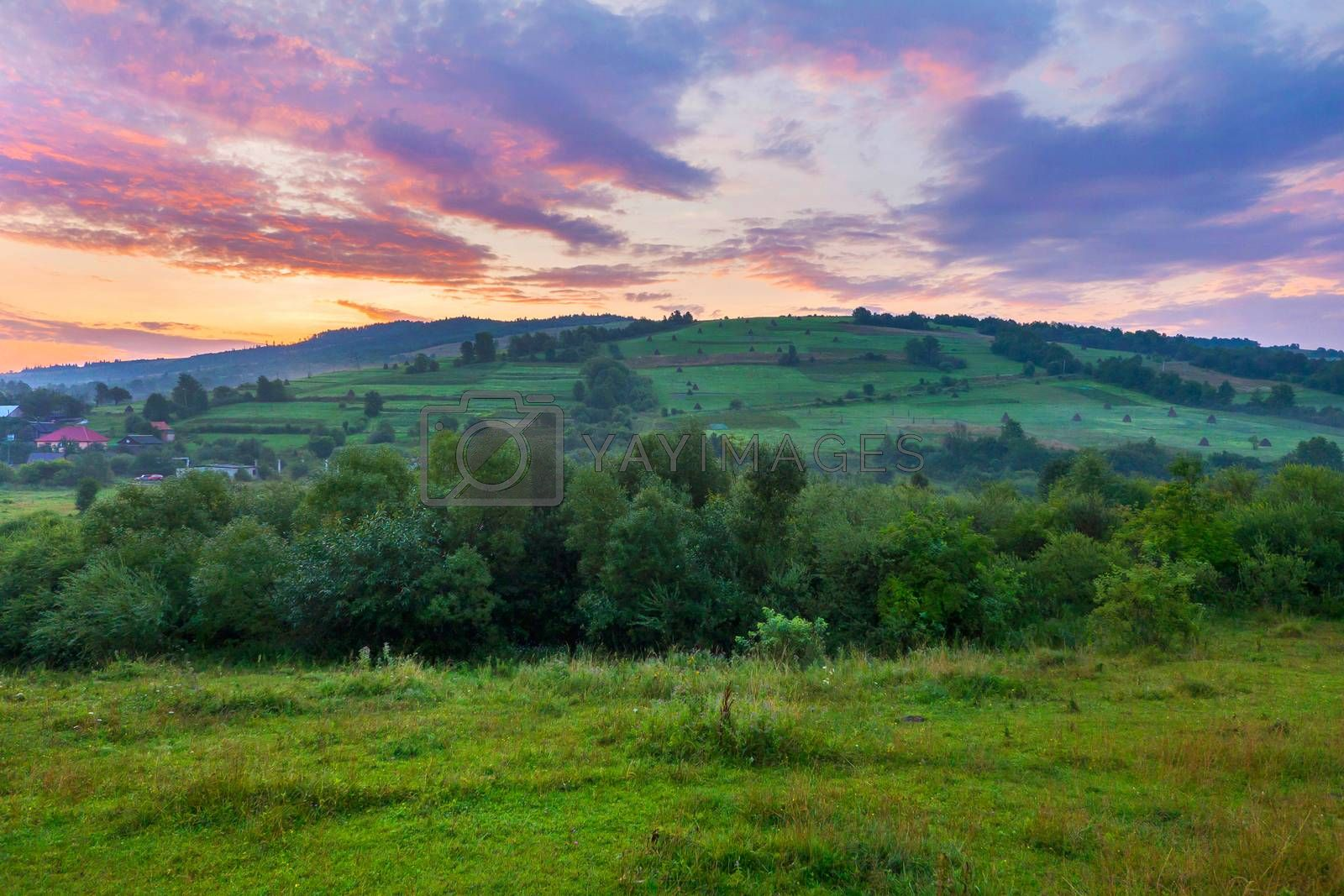 Green mountain slope with houses on it against the background of a dawn or sunset sky. place for rest and travel