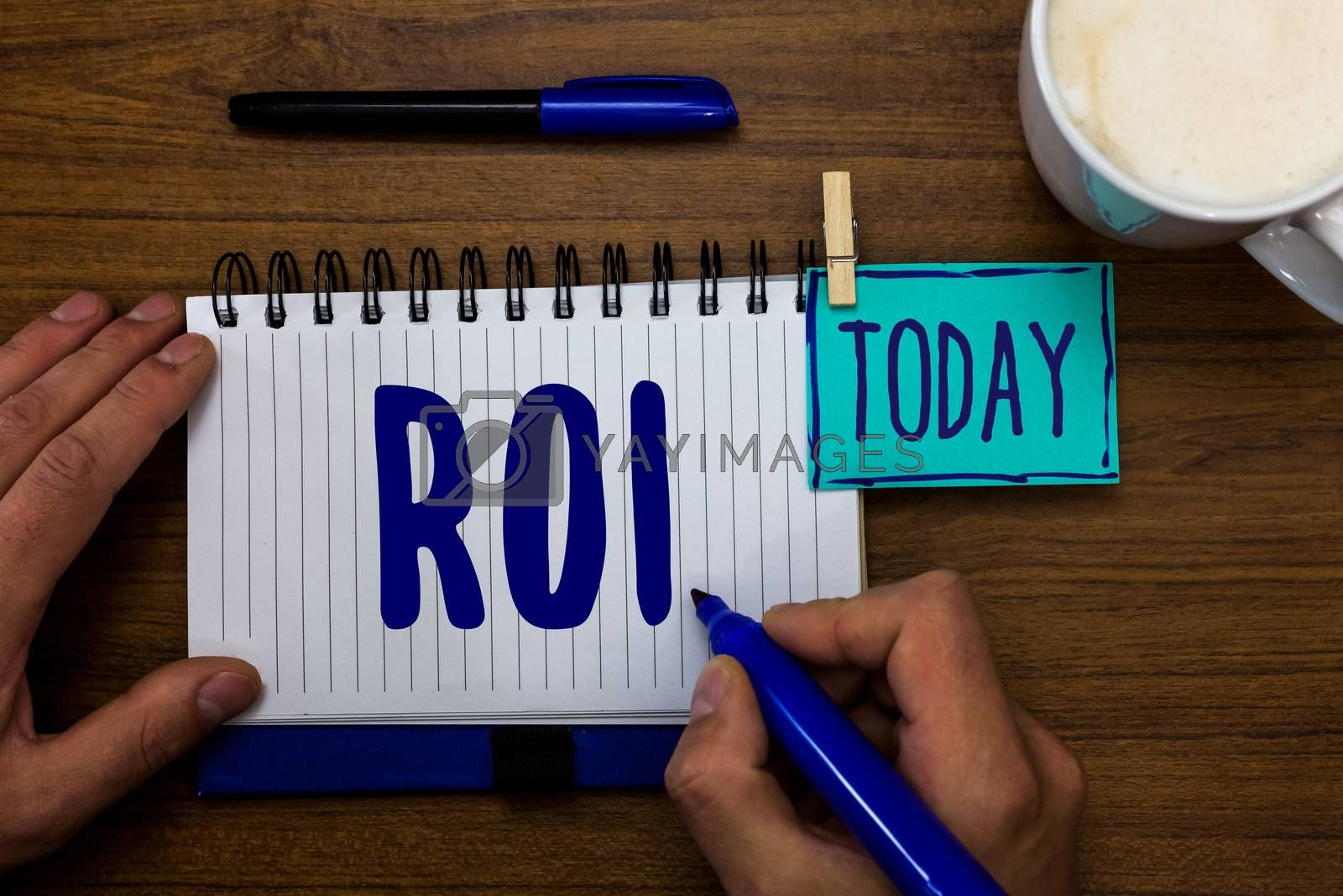 Handwriting text Roi. Concept meaning Return on investment performance measure gains business growth Marker pens notepad cup milk coffee daily memories dairy clip paperclip