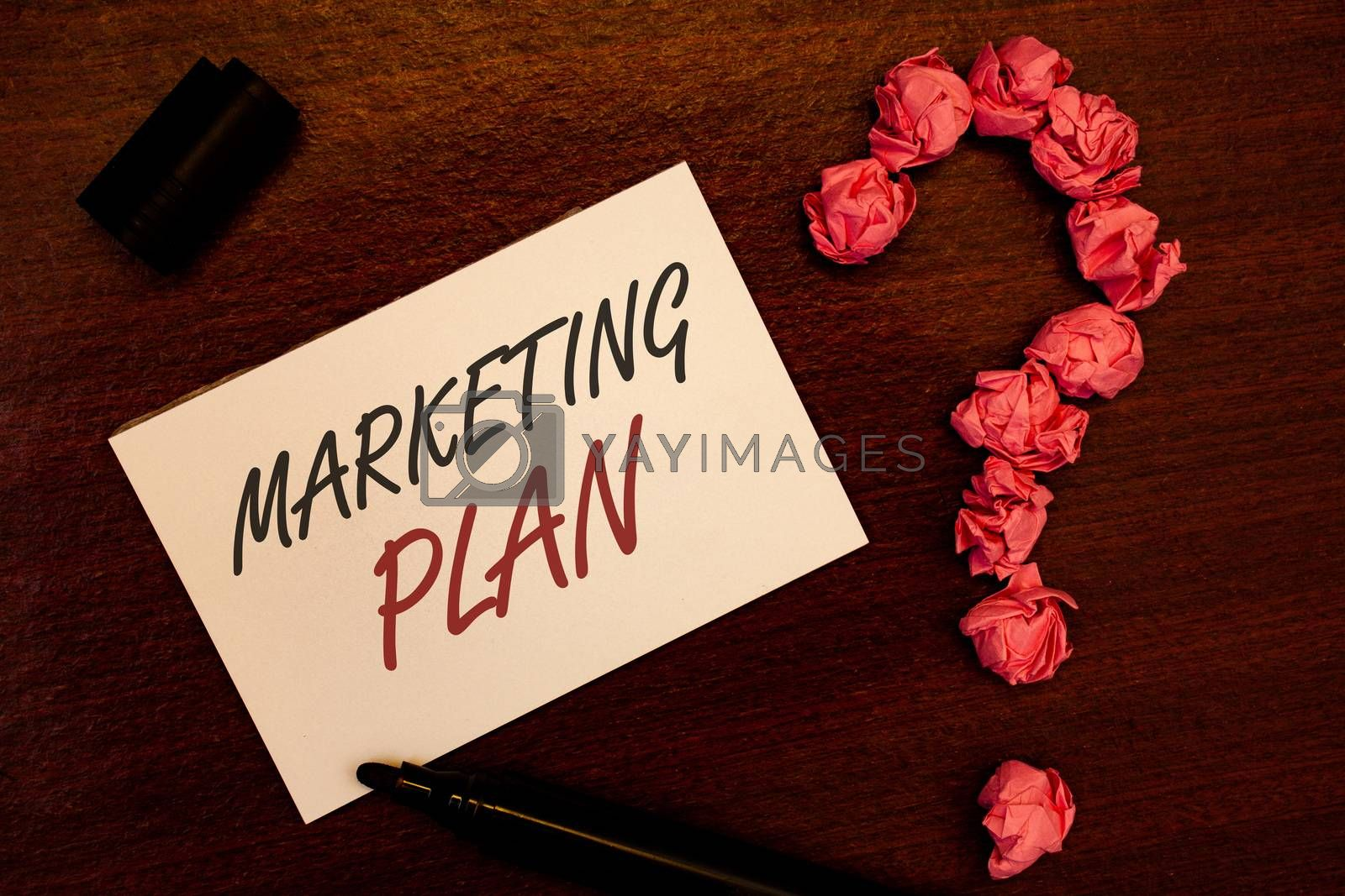 Text sign showing Marketing Plan. Conceptual photo Business Advertising Strategies Market Successful Ideas Text white paper note black marker open cap pink crumbled paper question