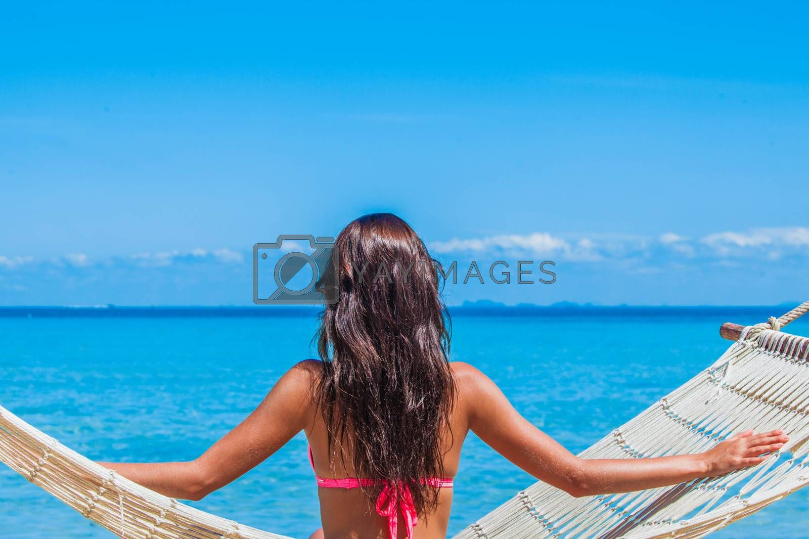 Young woman sitting in a hammock on a tropical beach and looking at sea