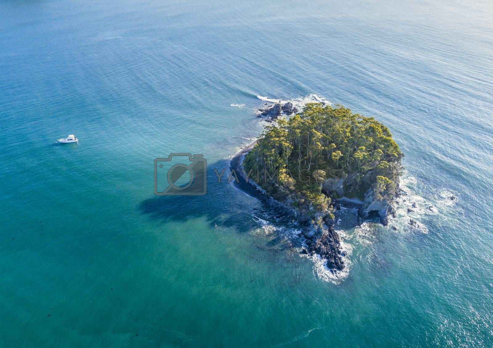 Aerial views of Snapper Island sitting 1 kilometre offshore in pristine aqua green waters of Batemans Bay Australia.  It lies a kilometre offshore and was a popular spot for smuggling as contraband could be hidden in the cave which had a back door escape route. Popular kayak or paddle venture.