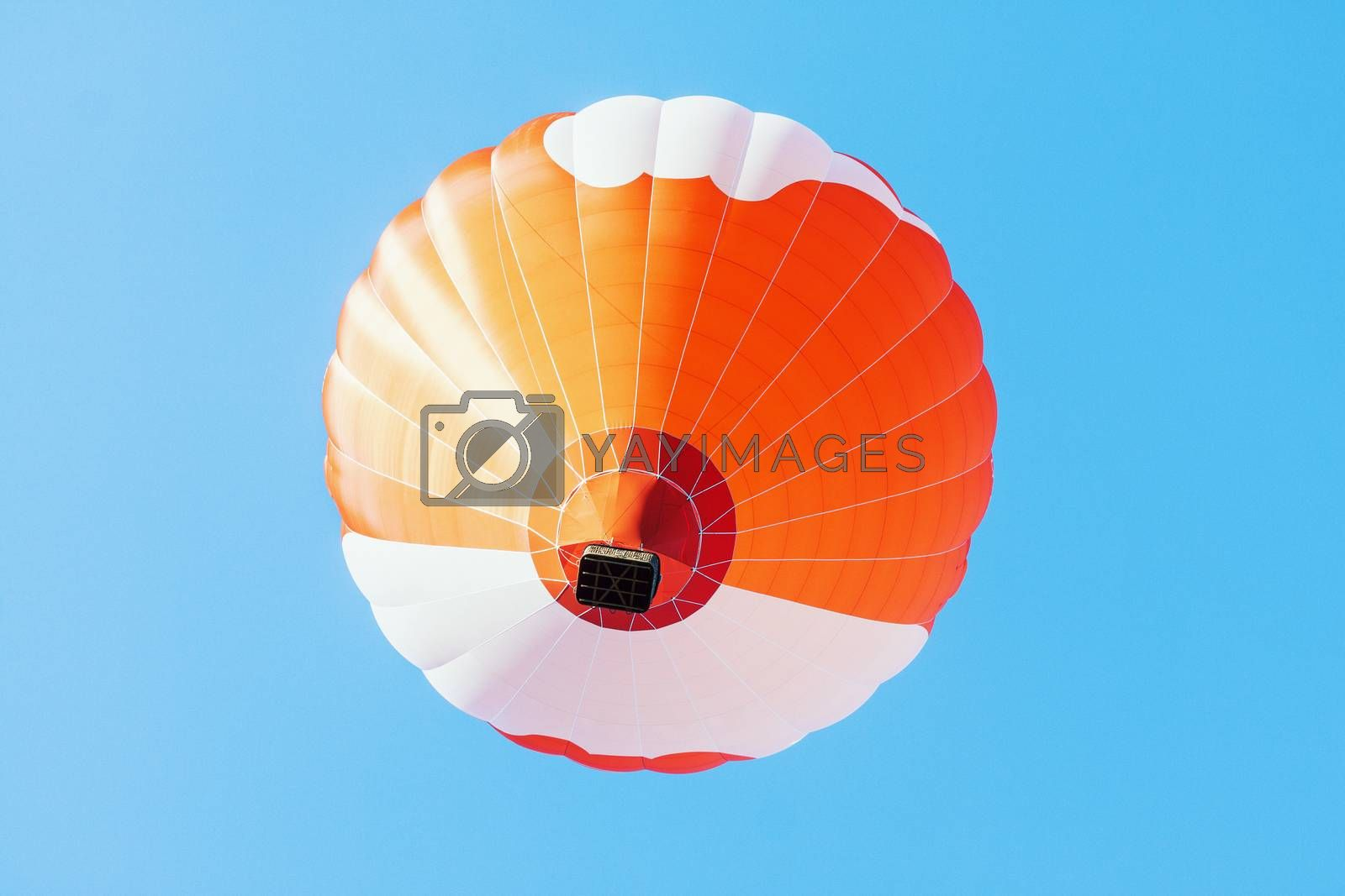 Colorful unbranded hot-air balloon flying in the background of blue sky, low angle picture