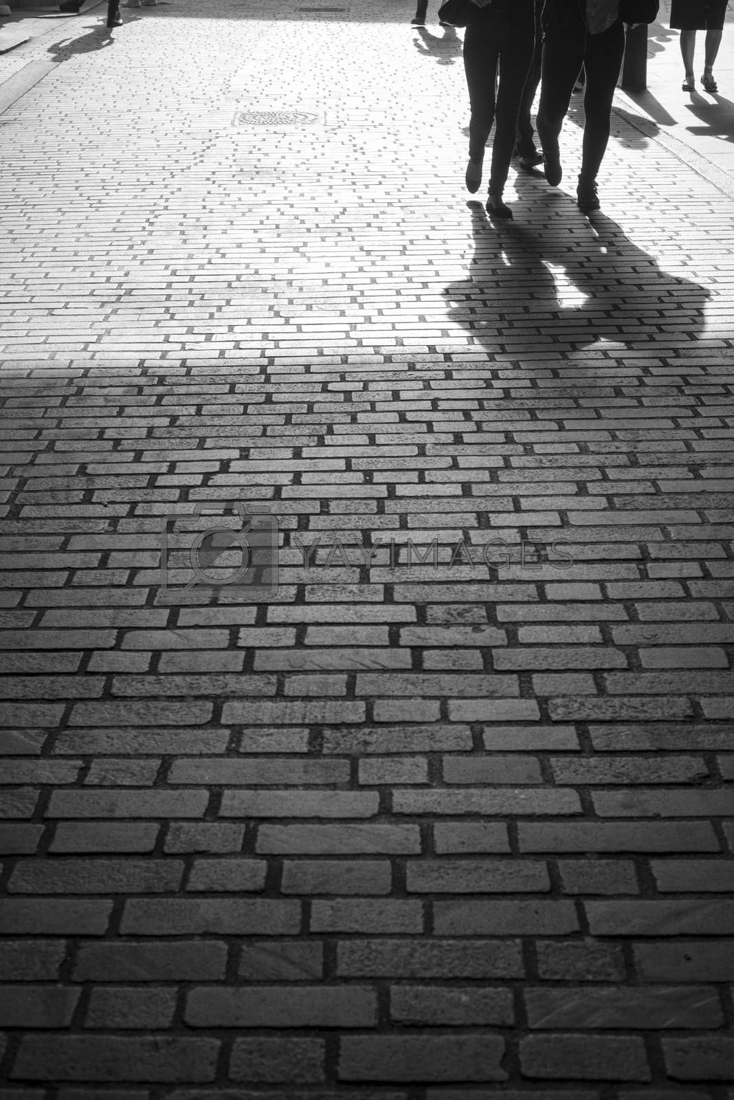 commuters walking down a cobbled lane in london city