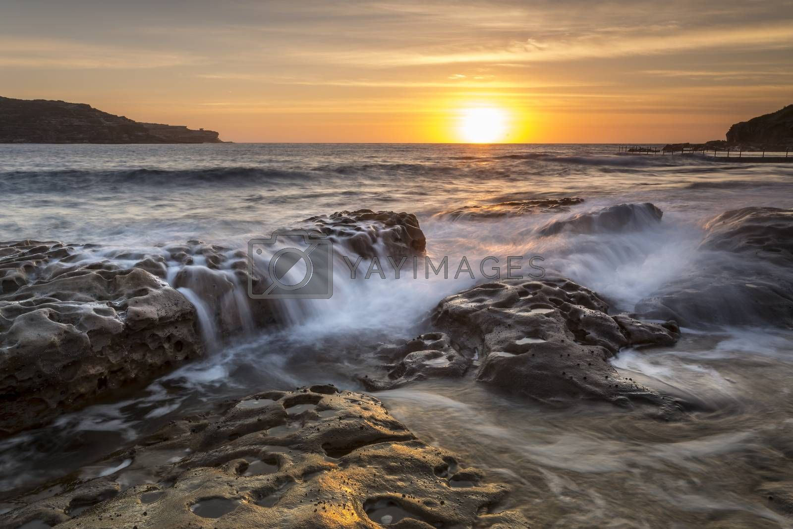 Sun rising on the horizon shining its golden light down Long Bay to Malabar with rock flows in the foreground.