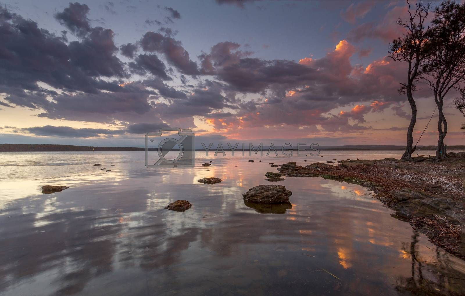 Tranquil sunset on the basin estuary with sunset reflections, the sound of gentle ripples and fish jumping