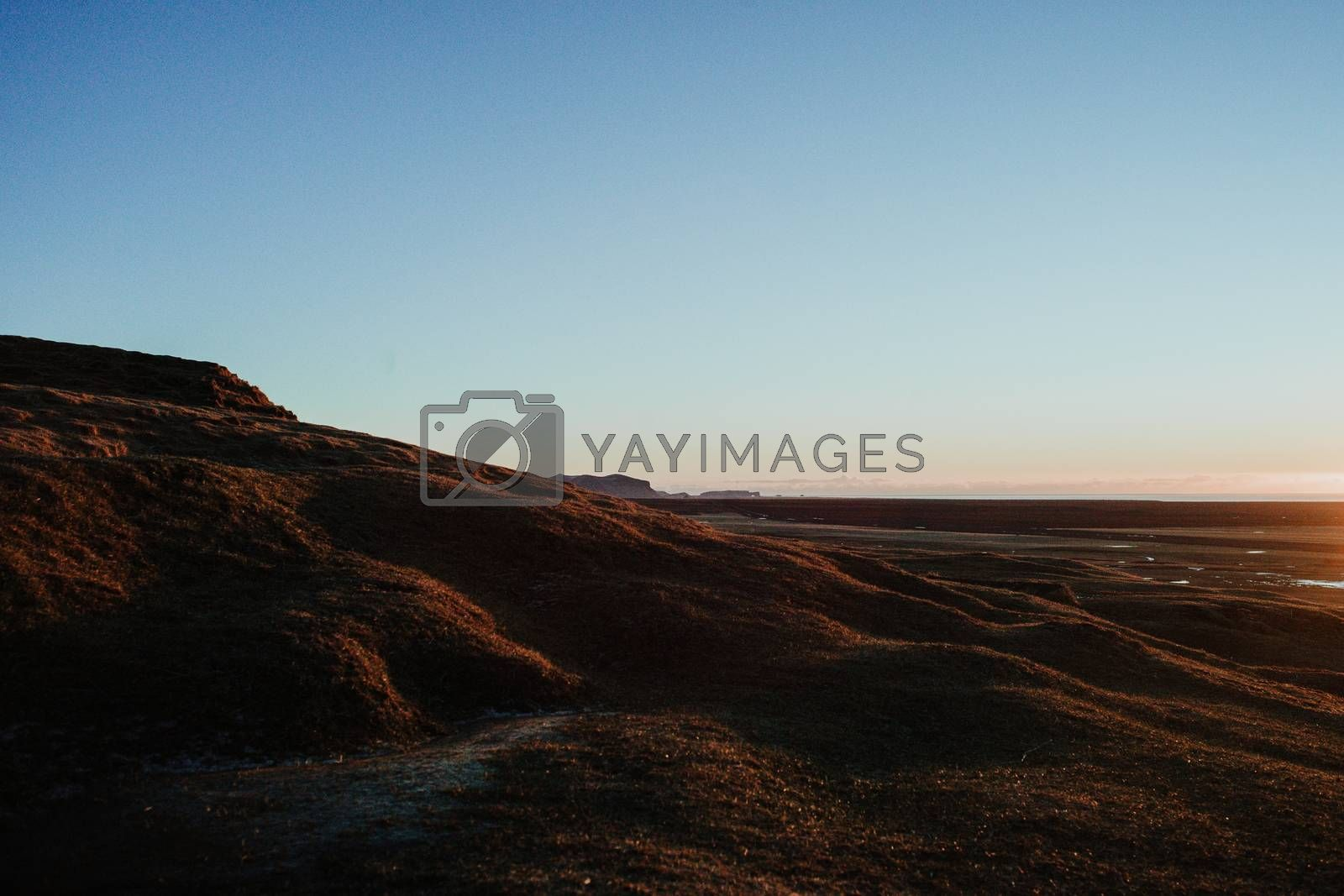 A landscape in Iceland at sunrise close to the famous waterfall Skogafoss