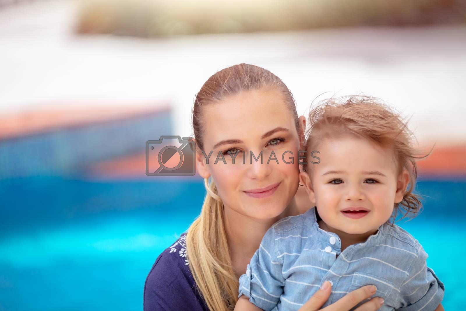 Portrait of a beautiful young mother with cute little son with pleasure spending time outdoors, happy family together, love concept