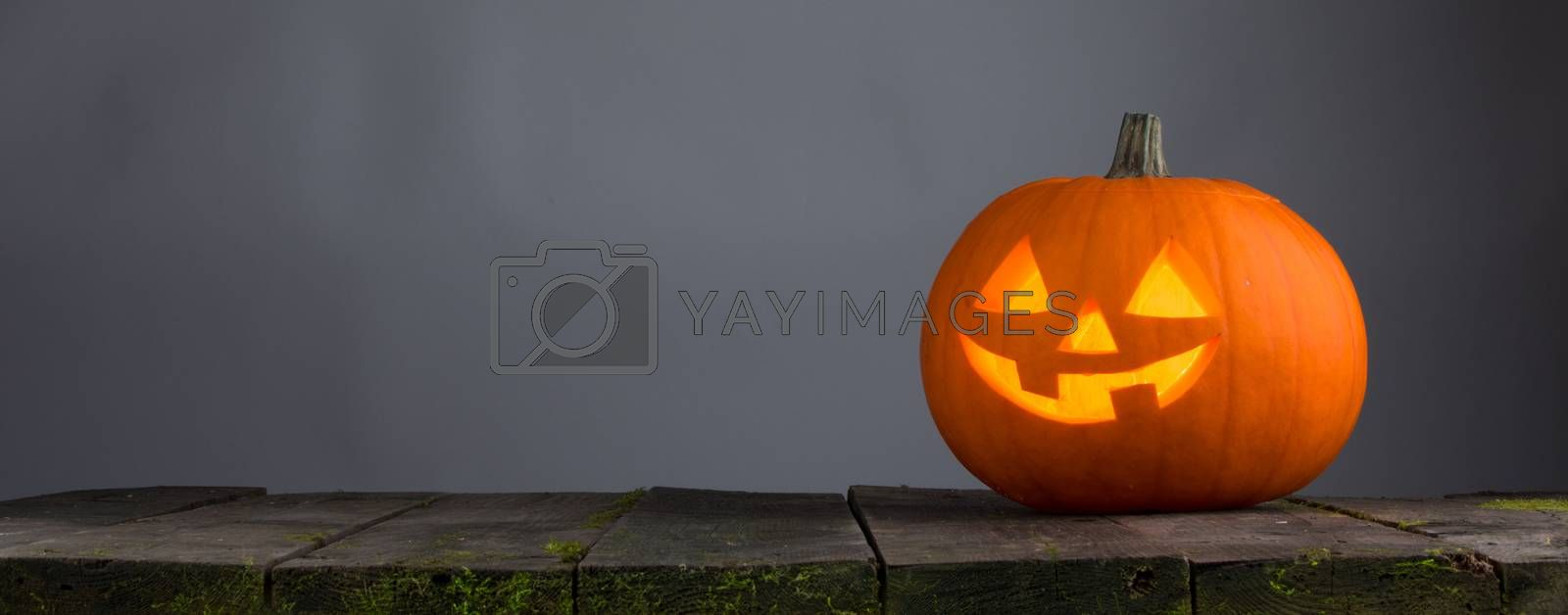 Glowing Halloween pumpkin head jack lantern on wooden table