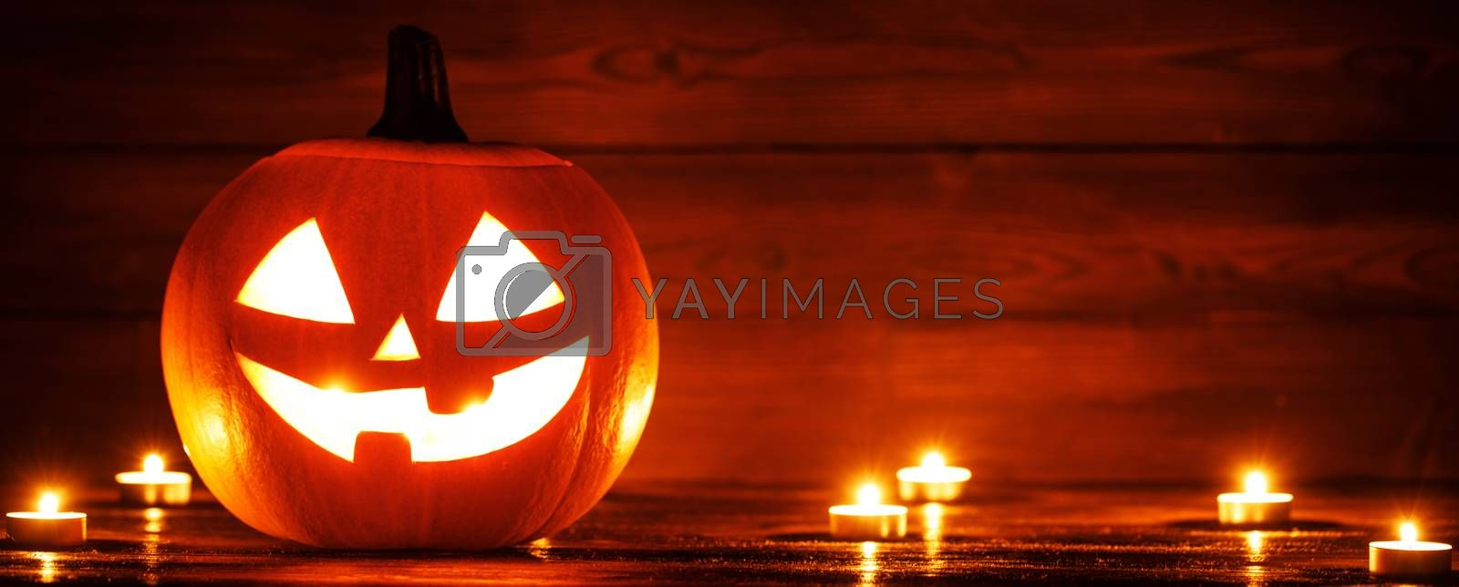 Halloween pumpkin head jack lantern and candles on wooden background