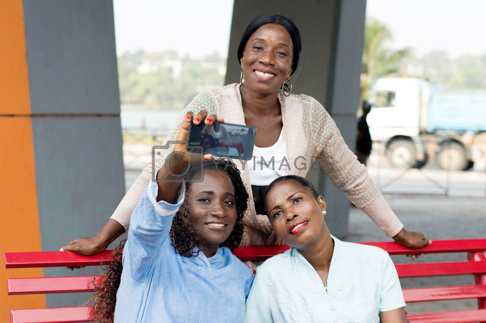 These young women sitting on a bench are photographed with a cell phone.