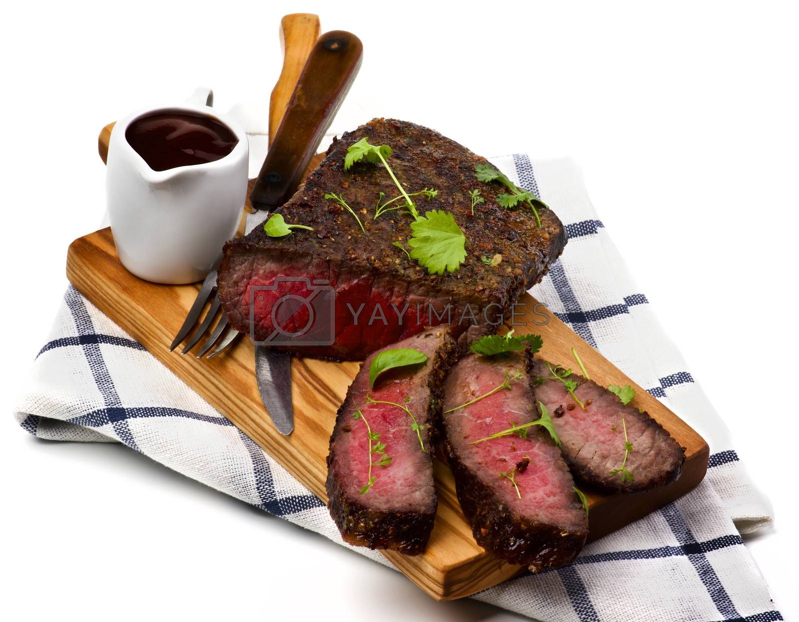 Delicious Roast Beef Medium Rare Sliced on Wooden Cutting Board with Tomato Sauce, Fork and Table Knife on Checkered Napkin closeup on White background