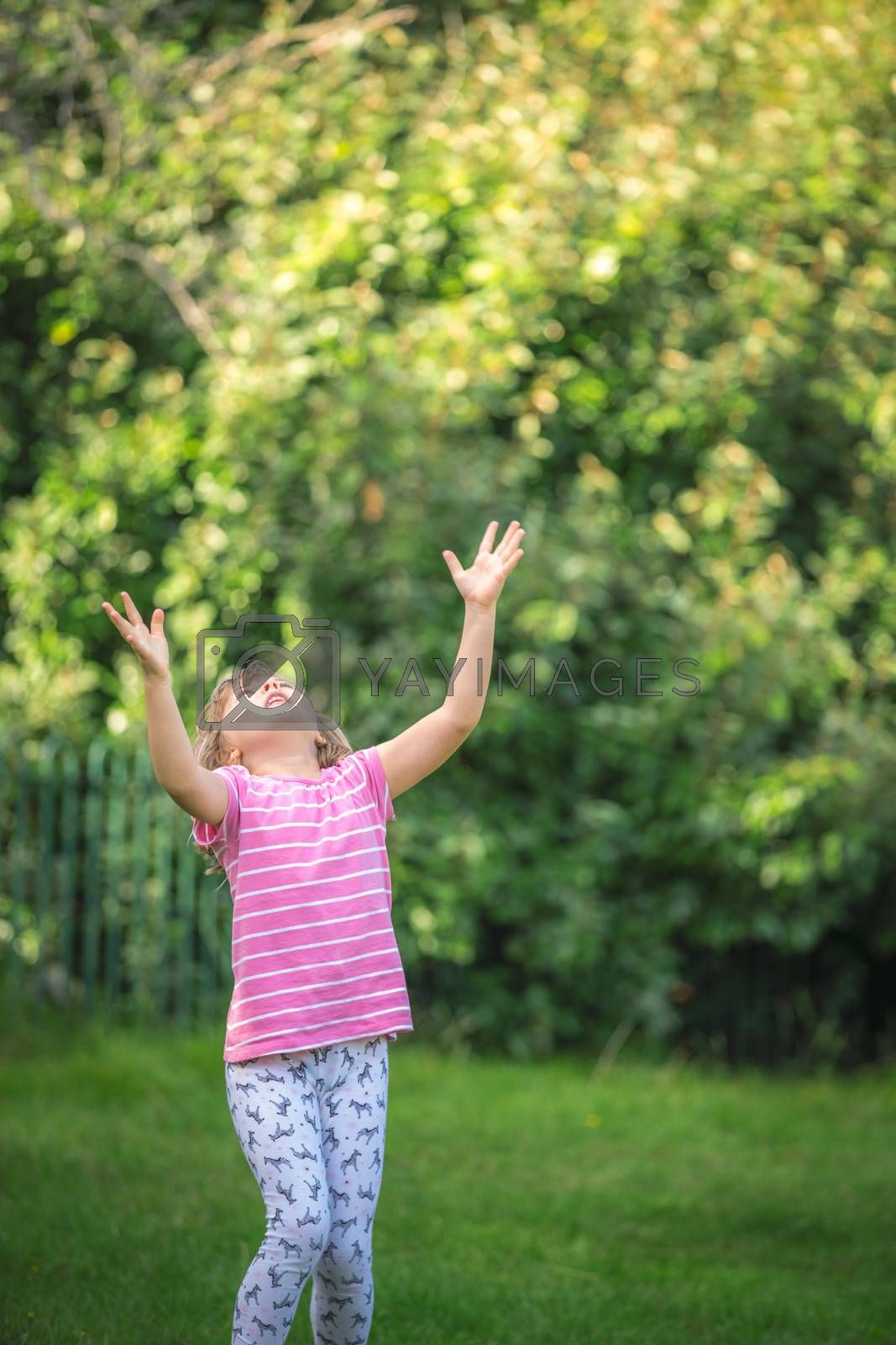 Little girl with arm spread open trying to catch the ball thrown high in the air