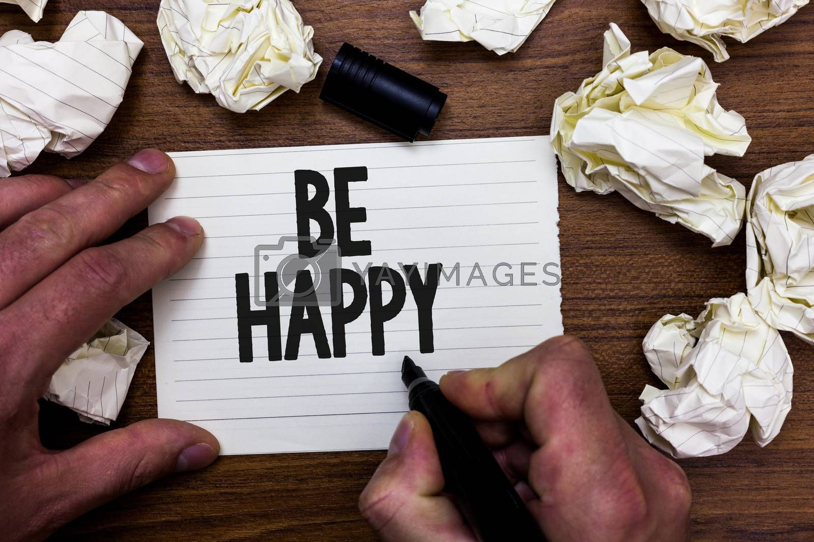 Word writing text Be Happy. Business concept for live every moment as the last love your life work family Man holding marker notebook page crumpled papers several tries mistakes