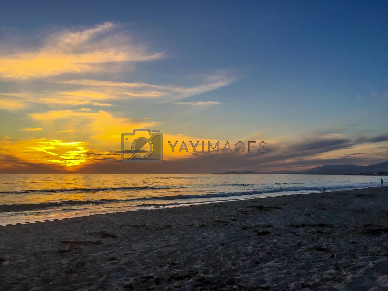 Romantic seaside sunset with orange and blue clouds in a sandy beach