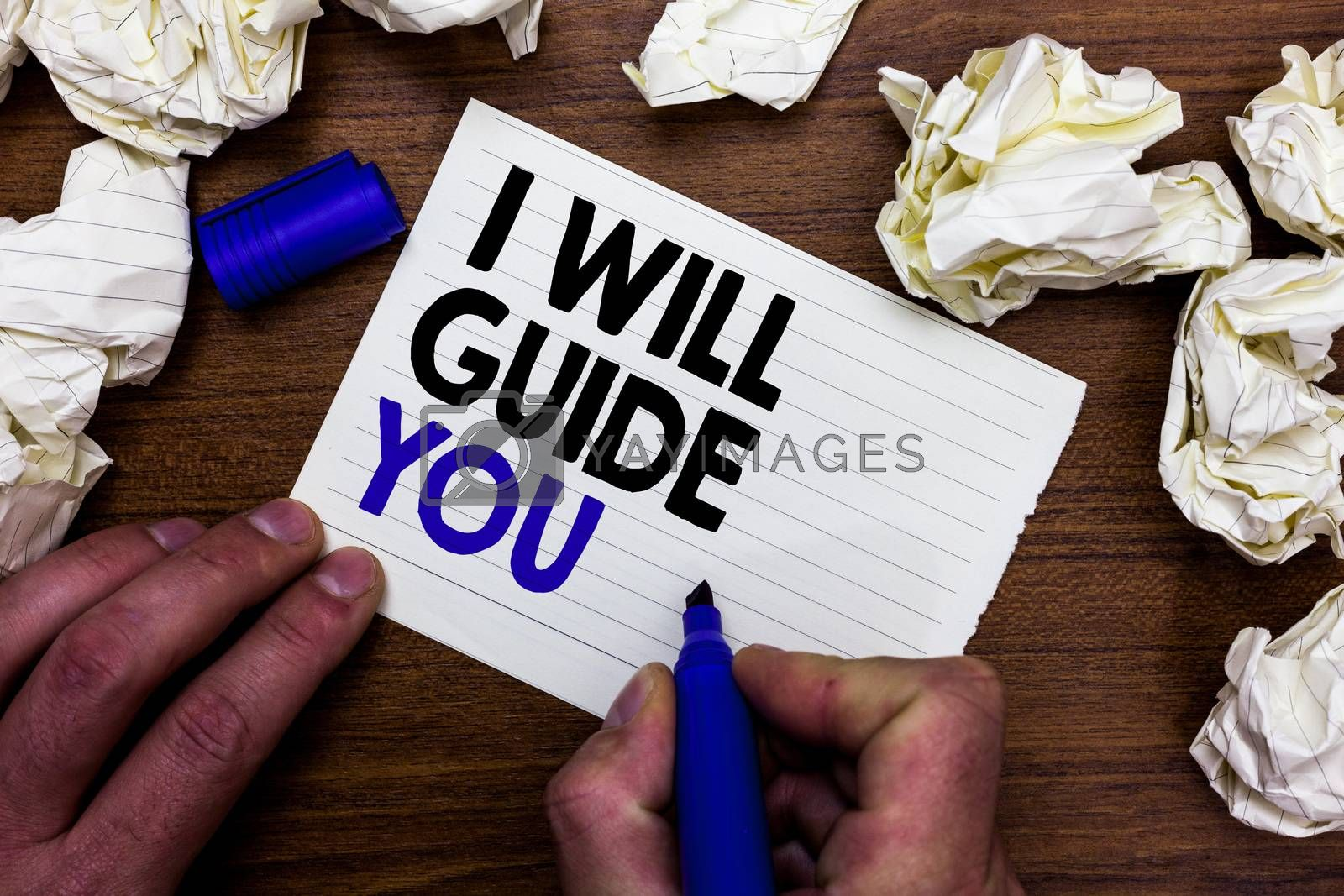 Writing note showing I Will Guide You. Business photo showcasing Help showing a route Influence to do or think something Hand holding marker write words paper lob scatter around woody desk