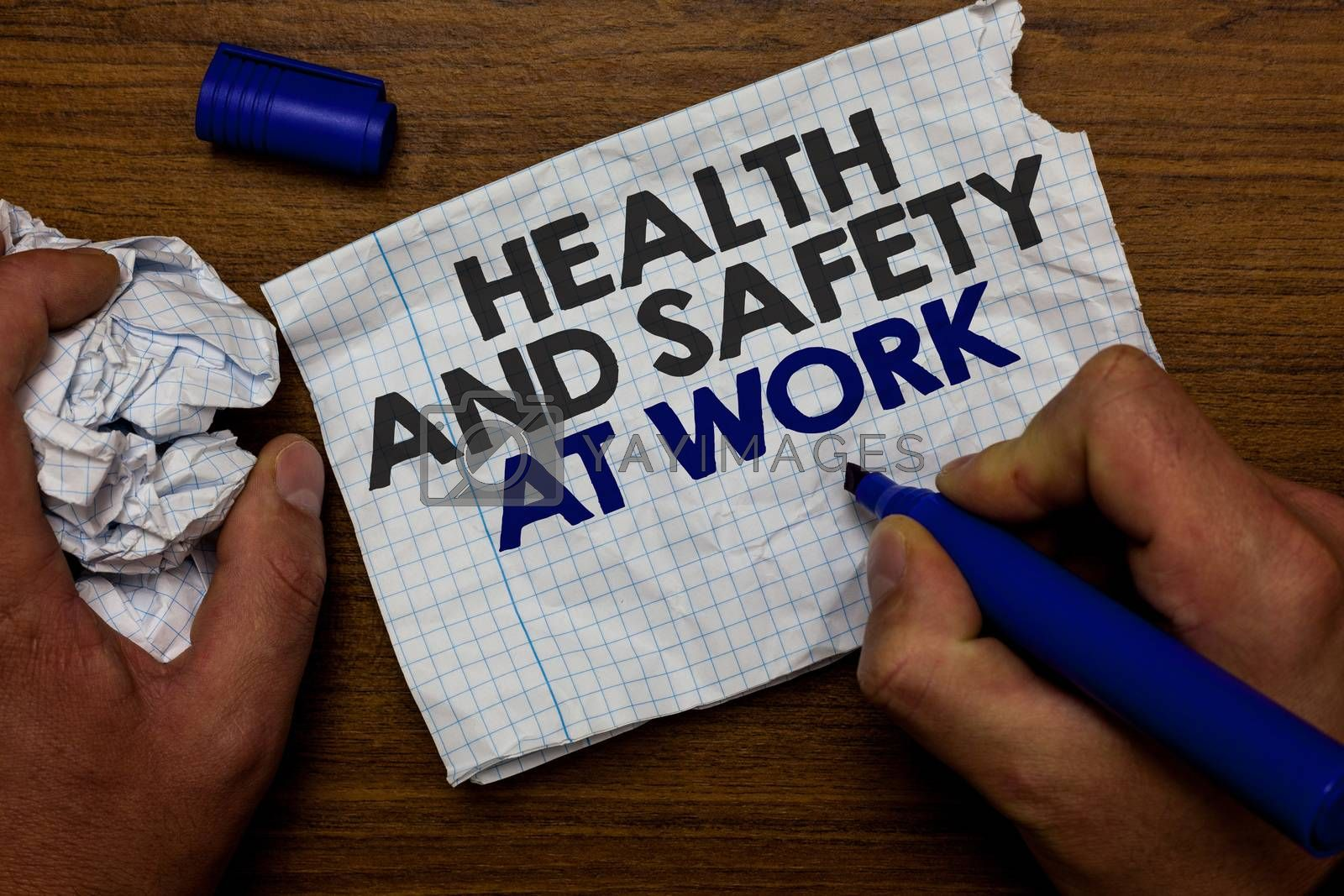 Word writing text Health And Safety At Work. Business concept for Secure procedures prevent accidents avoid danger Hand hold paper lob and blue marker wooden base with torn white written page