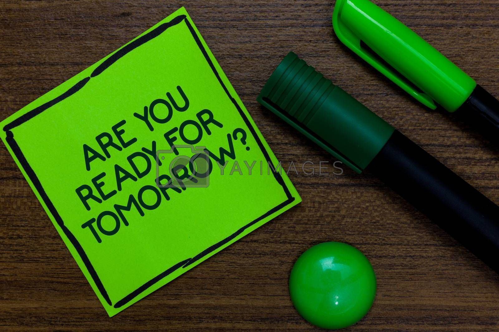 Text sign showing Are You Ready For Tomorrow question. Conceptual photo Preparation to the future Motivation Written on sticky note two markers laid on wooden floor green ball