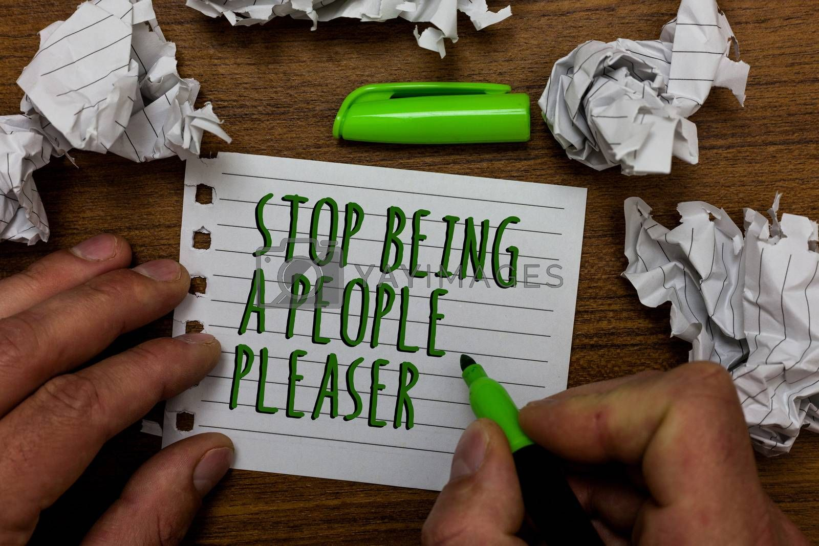 Word writing text Stop Being A People Pleaser. Business concept for Do what you like not things other people want Hand hold green pen and words on white page paper lobs around on wooden desk