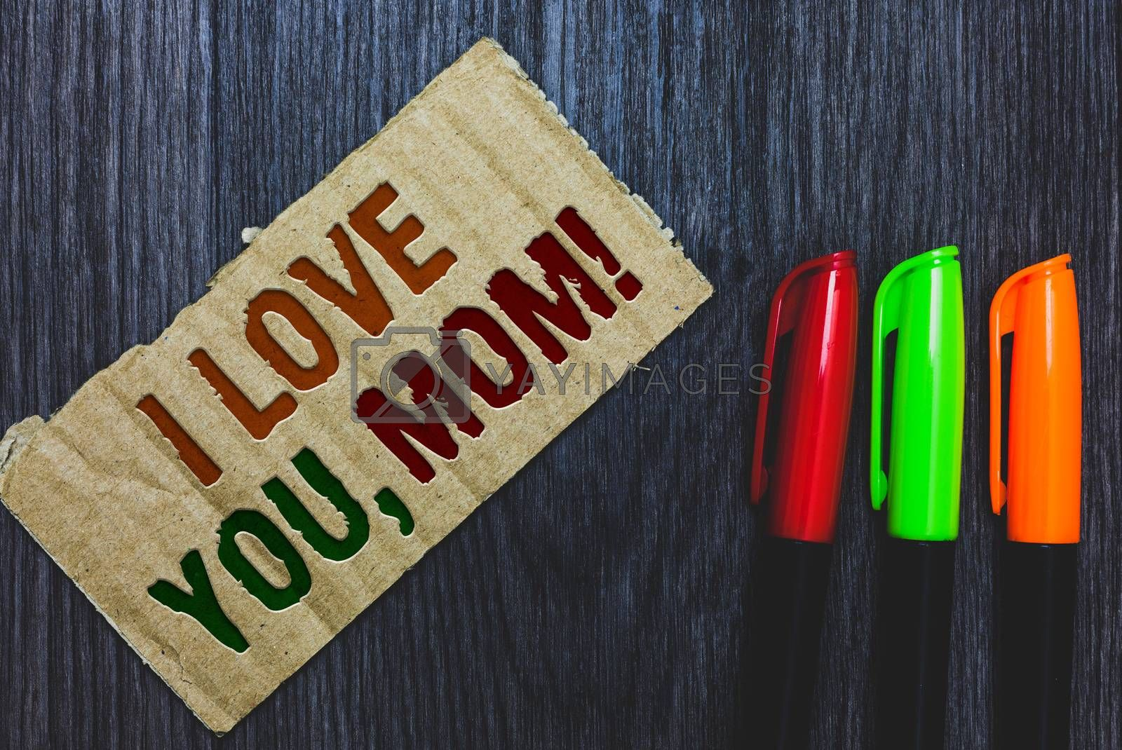 Writing note showing I Love You, Mom. Business photo showcasing Loving message emotional feelings affection warm declaration Cardboard with letters on grey wooden desk colorful pens laid rank. by Artur Szczybylo