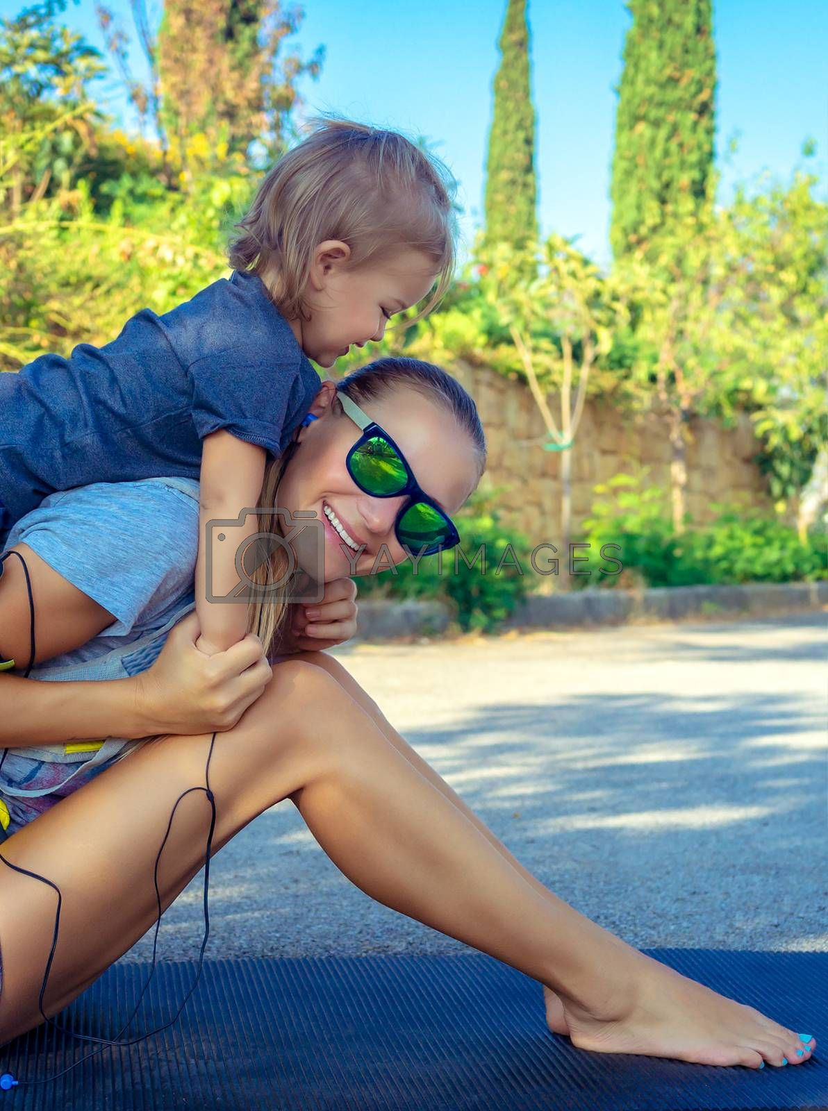 Portrait of a beautiful mom and her son playing sports games in the park on sunny summer day, happy active childhood, good loving family concept