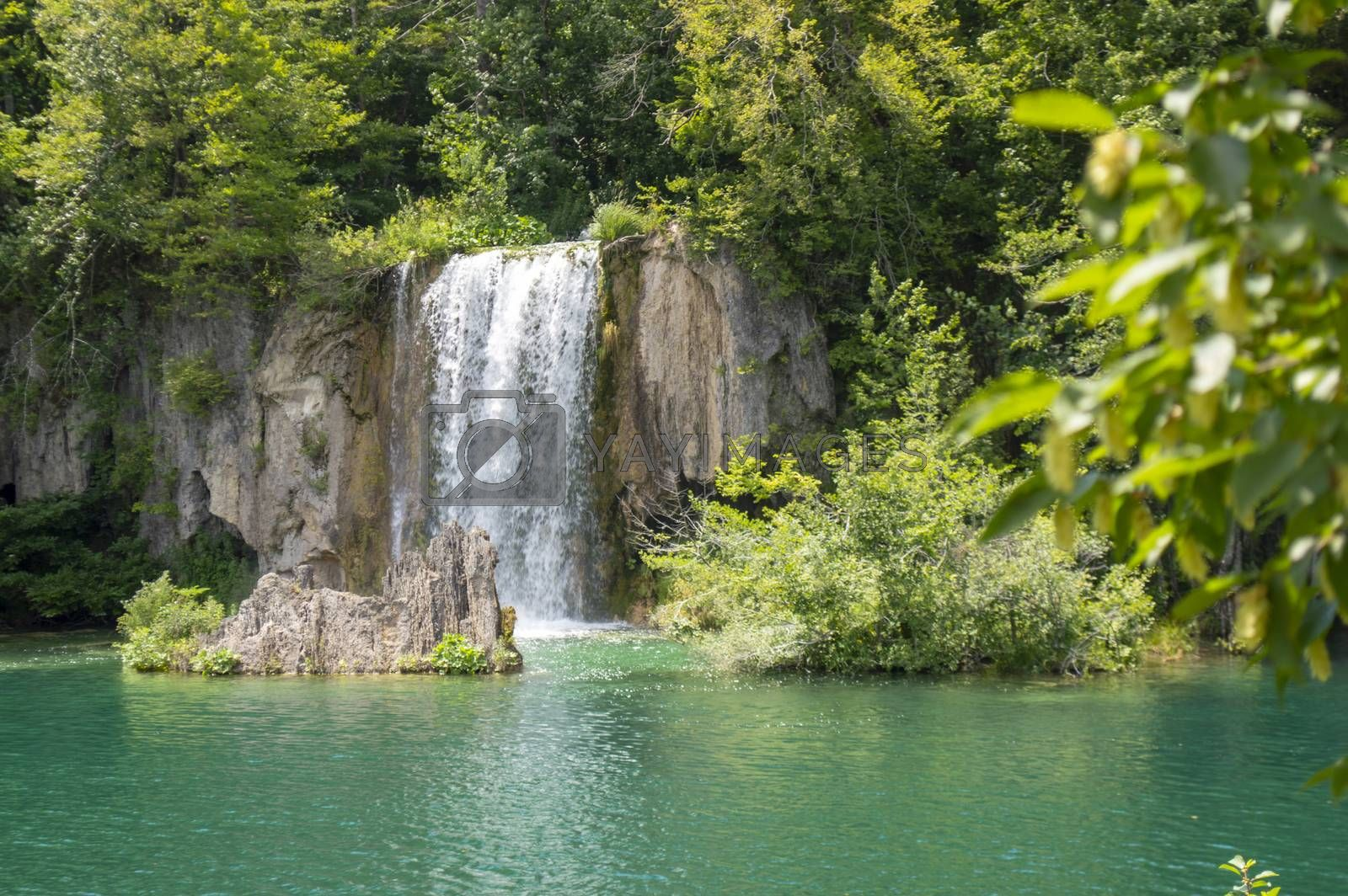 Beautiful waterfall, green trees and a blue lake in Plitvice tourist attraction.