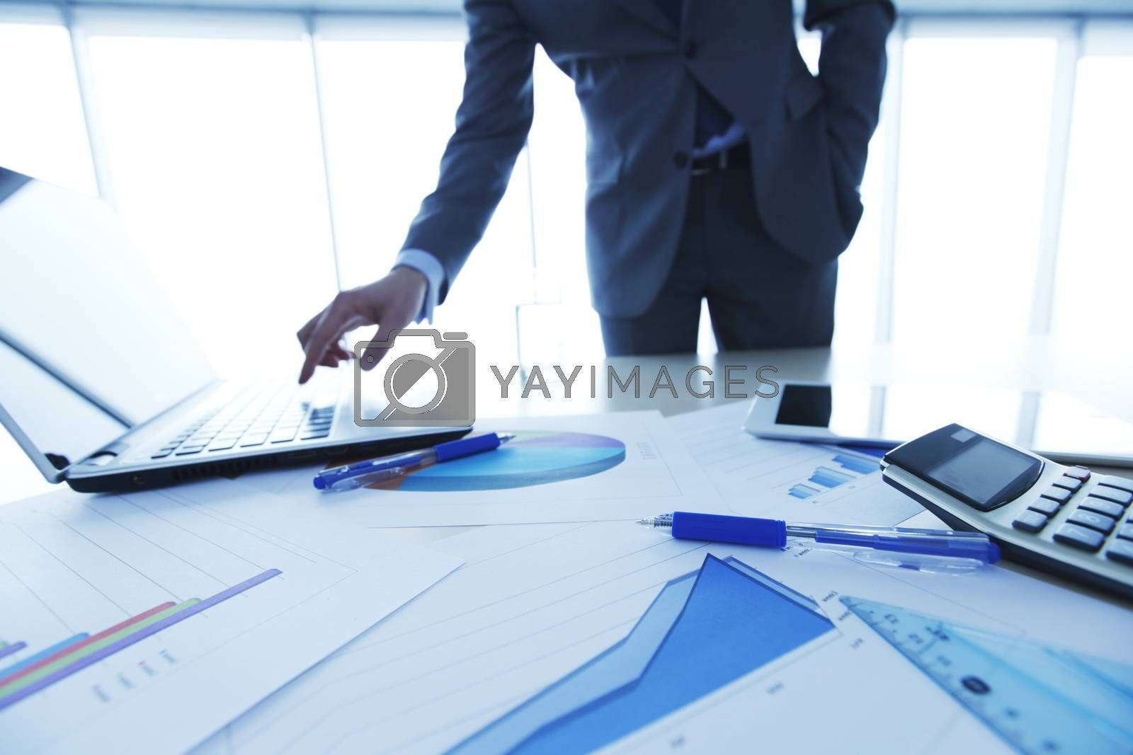 Businessman in office pressing key on laptop, financial data documents on the table