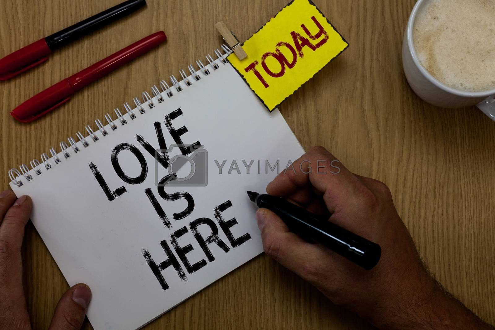 Handwriting text writing Love Is Here. Concept meaning Romantic feeling Lovely emotion Positive Expression Care Joy Man holding marker notebook clothespin reminder wooden table cup coffee