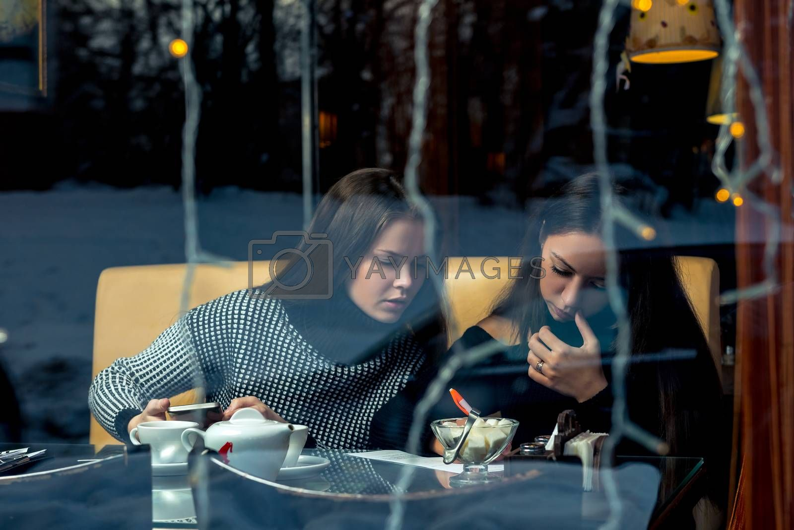 Communication of girlfriends, a meeting in a cafe, shooting behind a glass