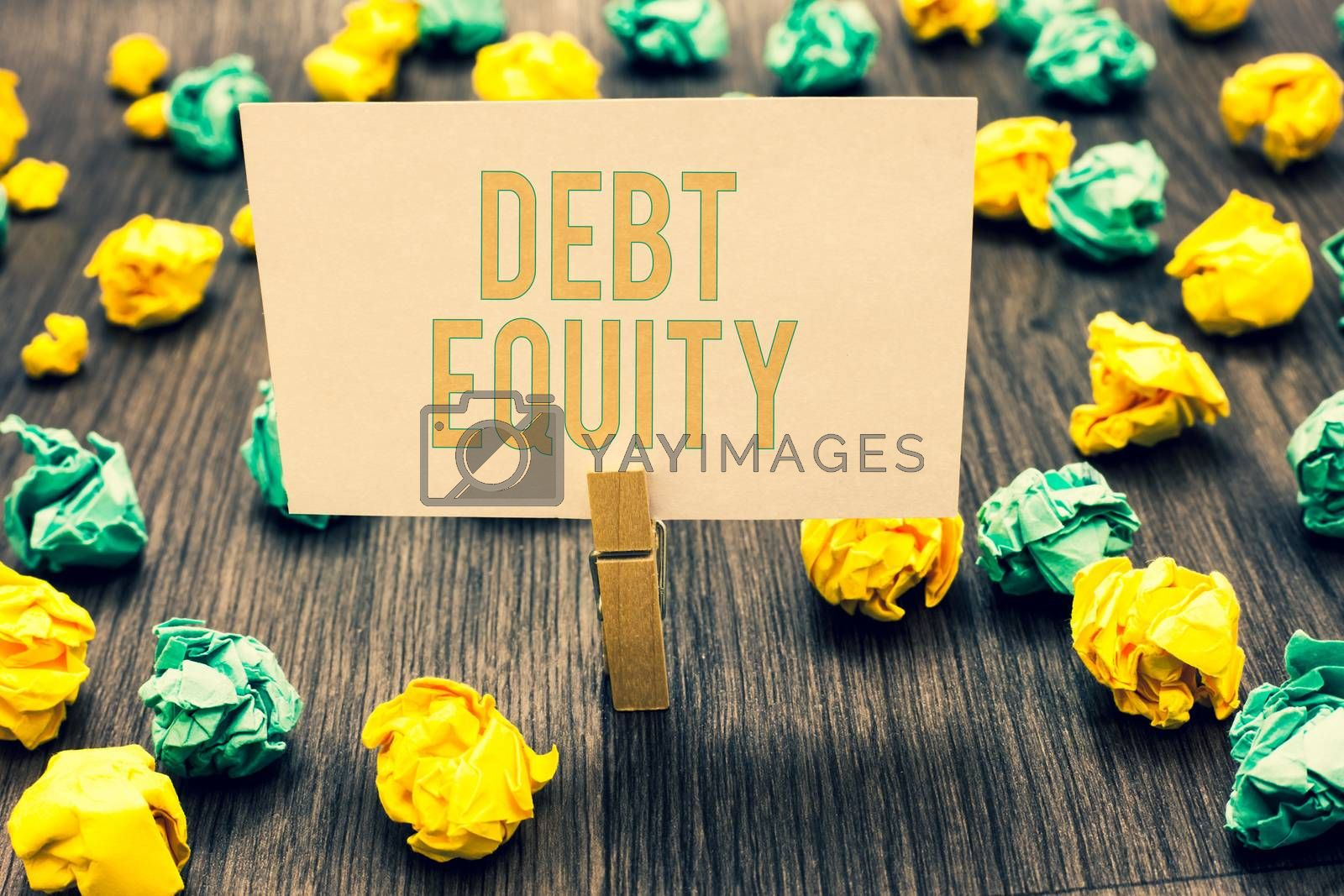 Handwriting text writing Debt Equity. Concept meaning dividing companys total liabilities by its stockholders Clothespin holding light pink note paper crumpled papers several tries