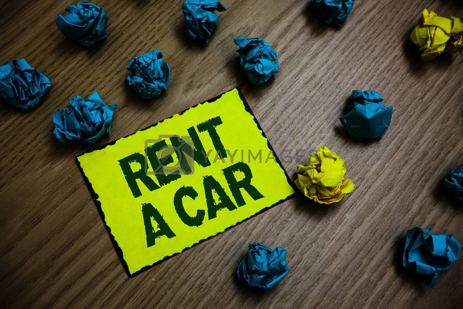 Word writing text Rent A Car. Business concept for paying for temporary vehicle usage from one day to months Yellow piece paper reminder lots crumpled papers several tries wooden floor