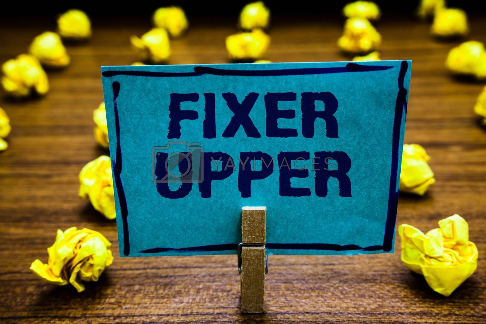 Word writing text Fixer Upper. Business concept for house in need of repairs used chiefly connection with purchase Clothespin holding blue paper note crumpled papers several tries mistakes