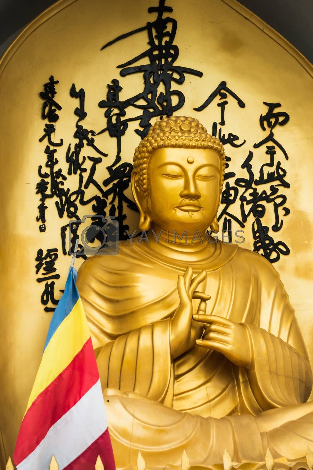 Golden Buddha statue and buddhist flag at the World Peace Pagoda in Pokhara, Nepal