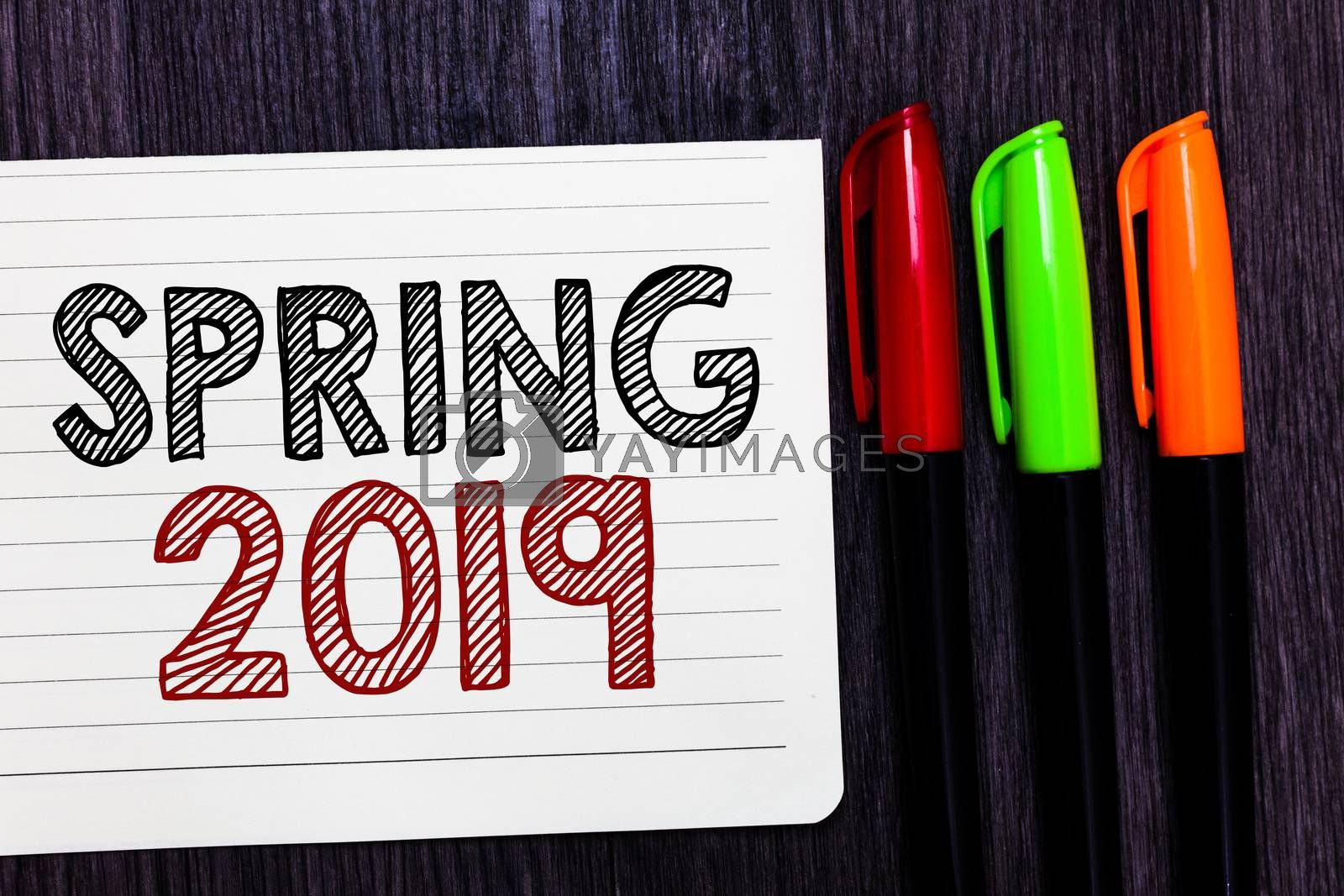 Word writing text Spring 2019. Business concept for time of year where flowers rise following winter season Notebook paper colorful markers wooden background communicating ideas