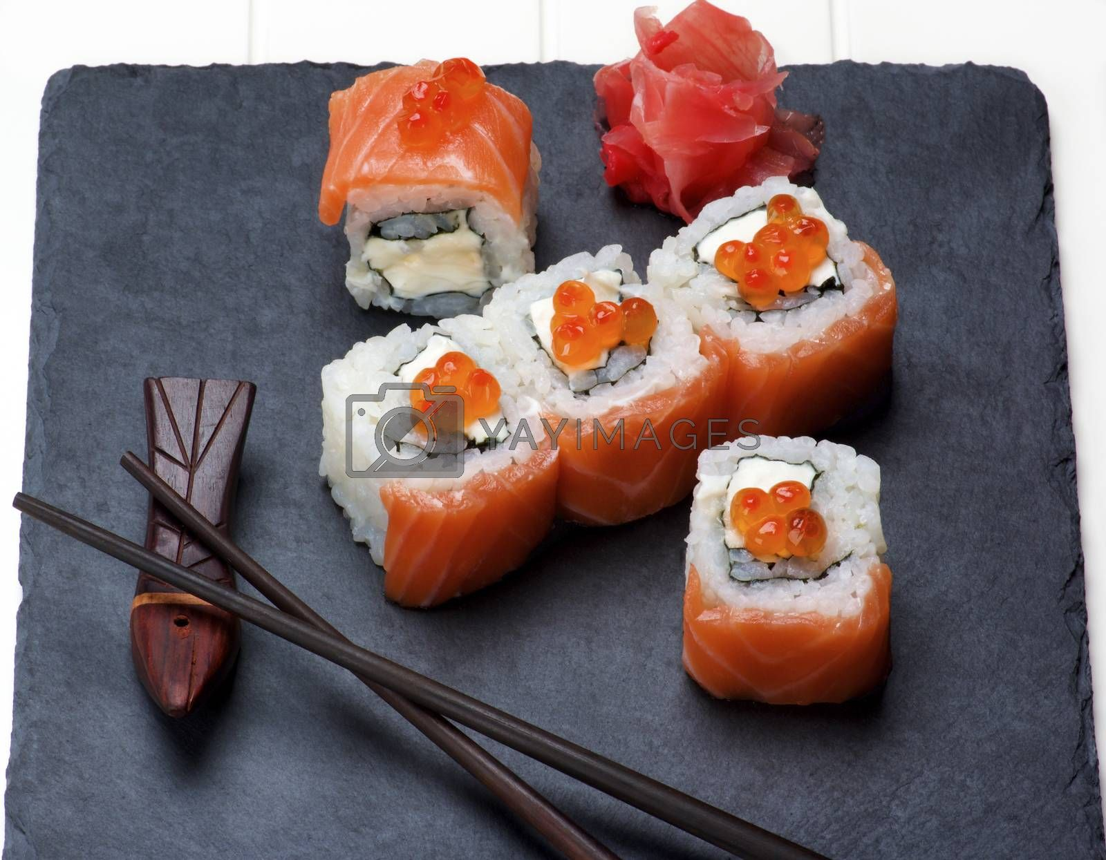 Delicious Sushi with Smoked Sliced Salmon and Gourmet Red Caviar on Serving Stone Plate with Chopsticks and Ginger closeup