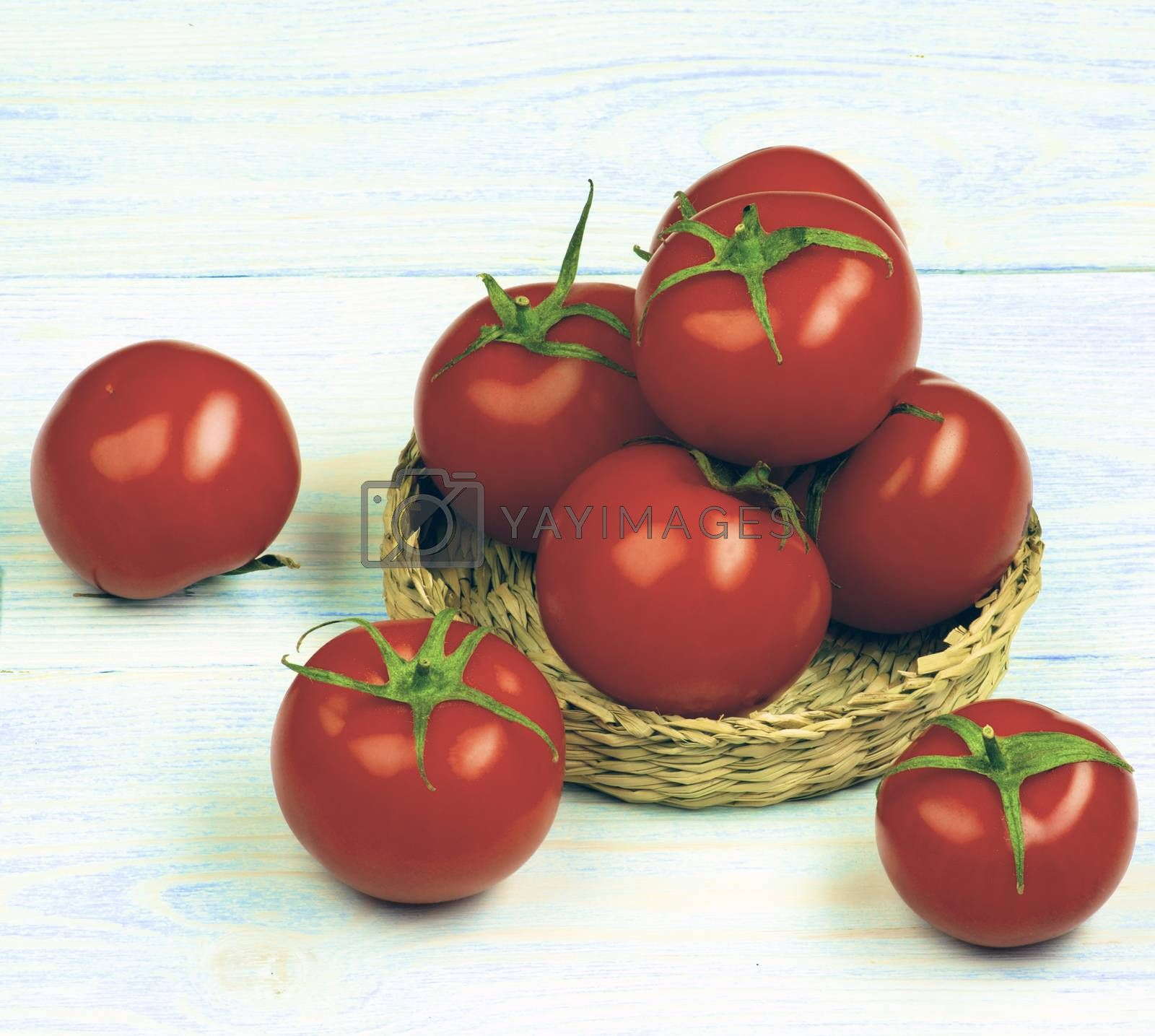 Heap of Ripe Raw Red Tomatoes with Stems in Wicker Plate closeup on Light Wooden background