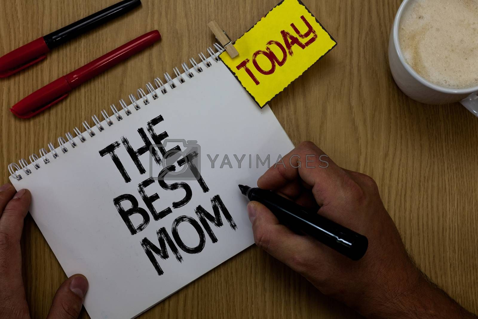 Handwriting text writing The Best Mom. Concept meaning Appreciation for your mother love feelings compliment Man holding marker notebook clothespin reminder wooden table cup coffee. by Artur Szczybylo