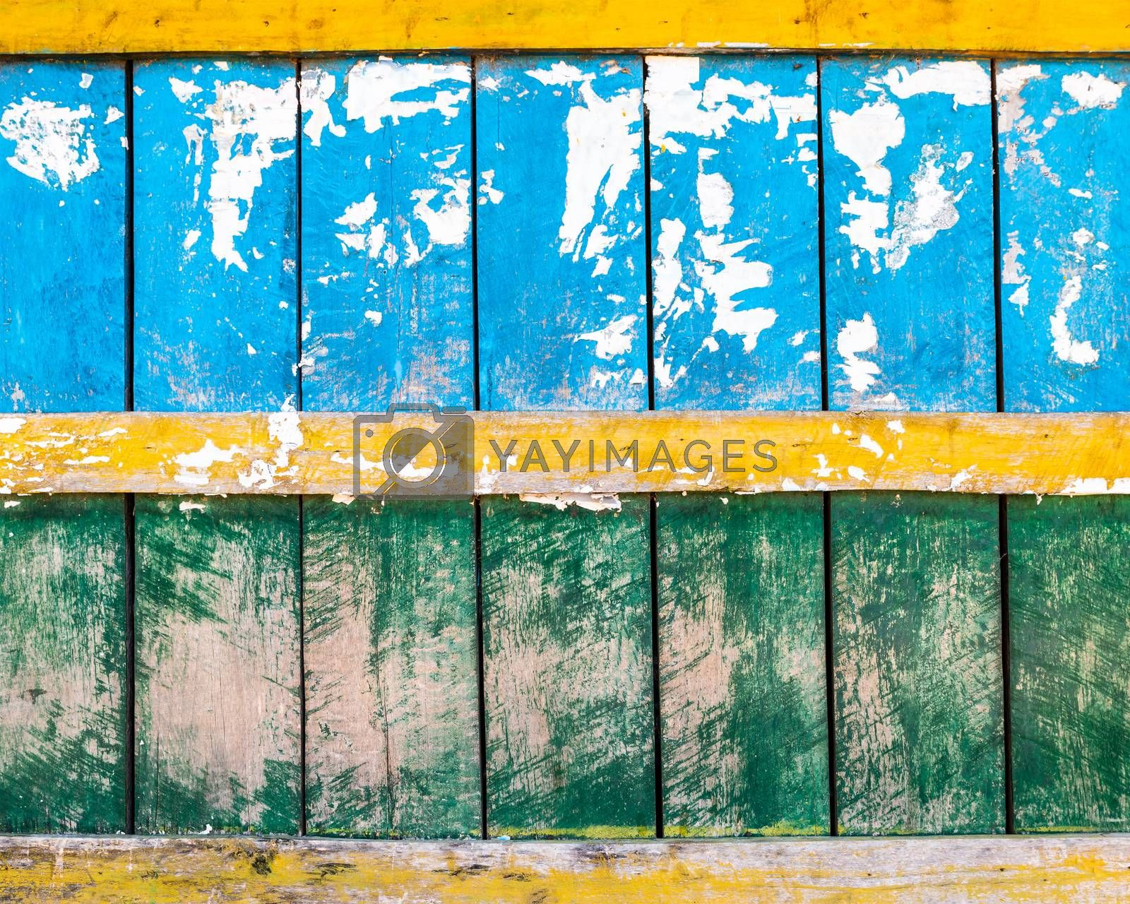 Grungy blue, green and yellow wood wall texture, torn paper in the top half