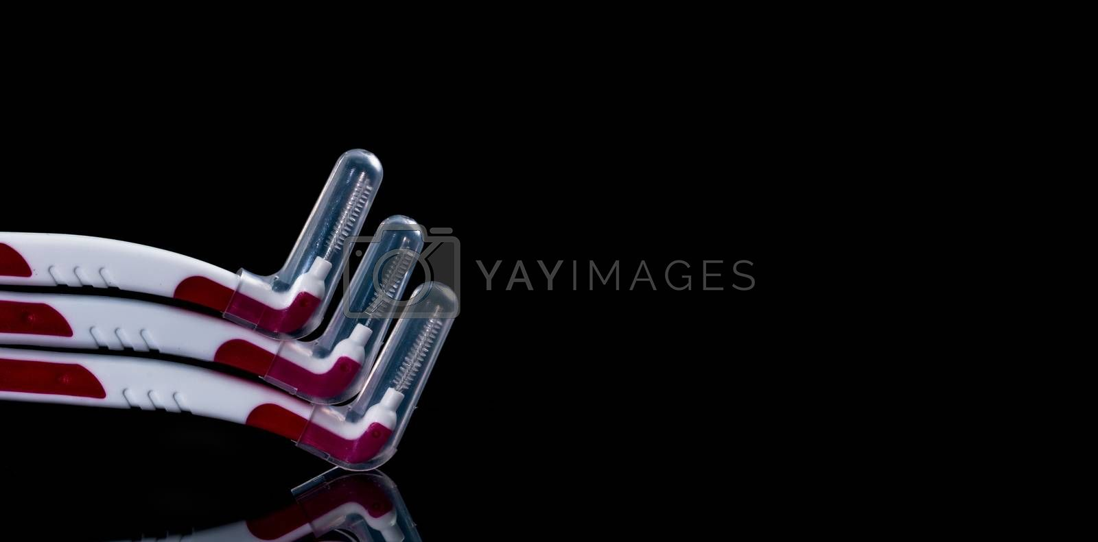 Three inter-dental brush with cover isolated on black background with copy space for text. Dental care concept. Equipment for get rid of food stuck in teeth