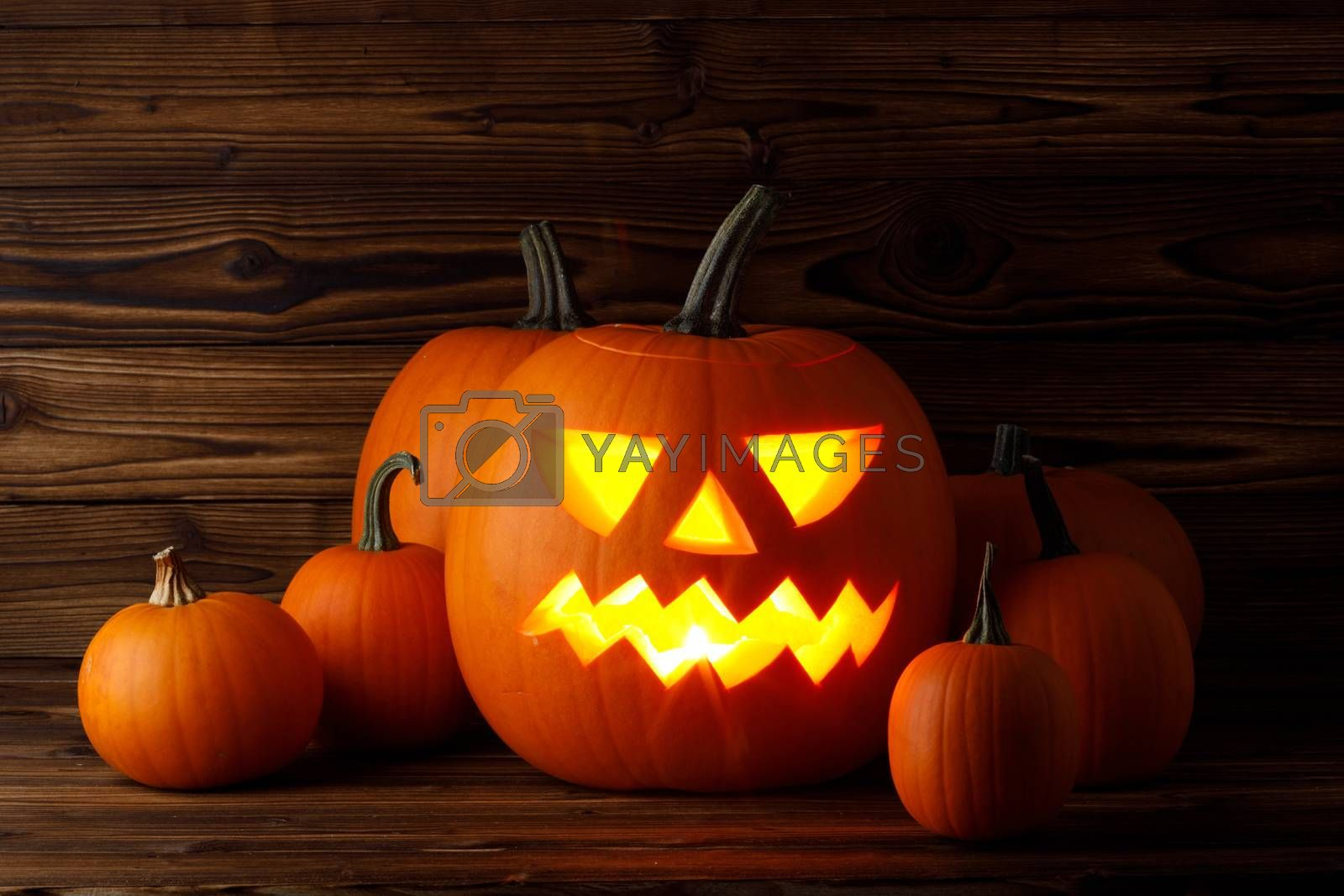 Glowing Halloween pumpkin heads jack o lantern on wooden background