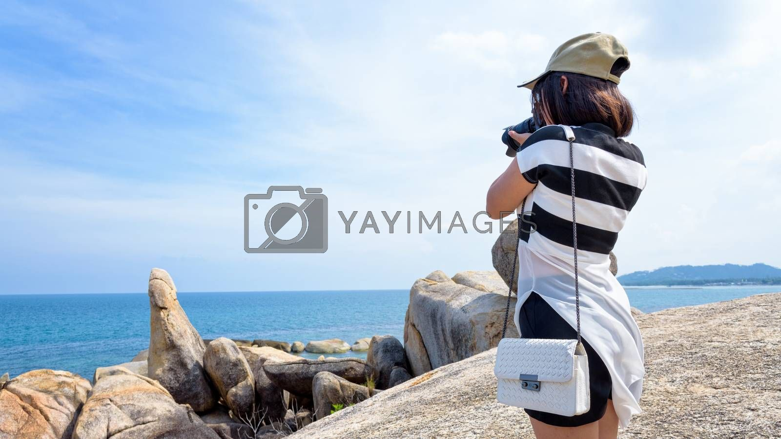 Young woman are using a DSLR camera to photography of the Hin Ta Hin Yai and beautiful nature landscape of blue sea and sky during summer travel at Koh Samui island, Surat Thani, Thailan