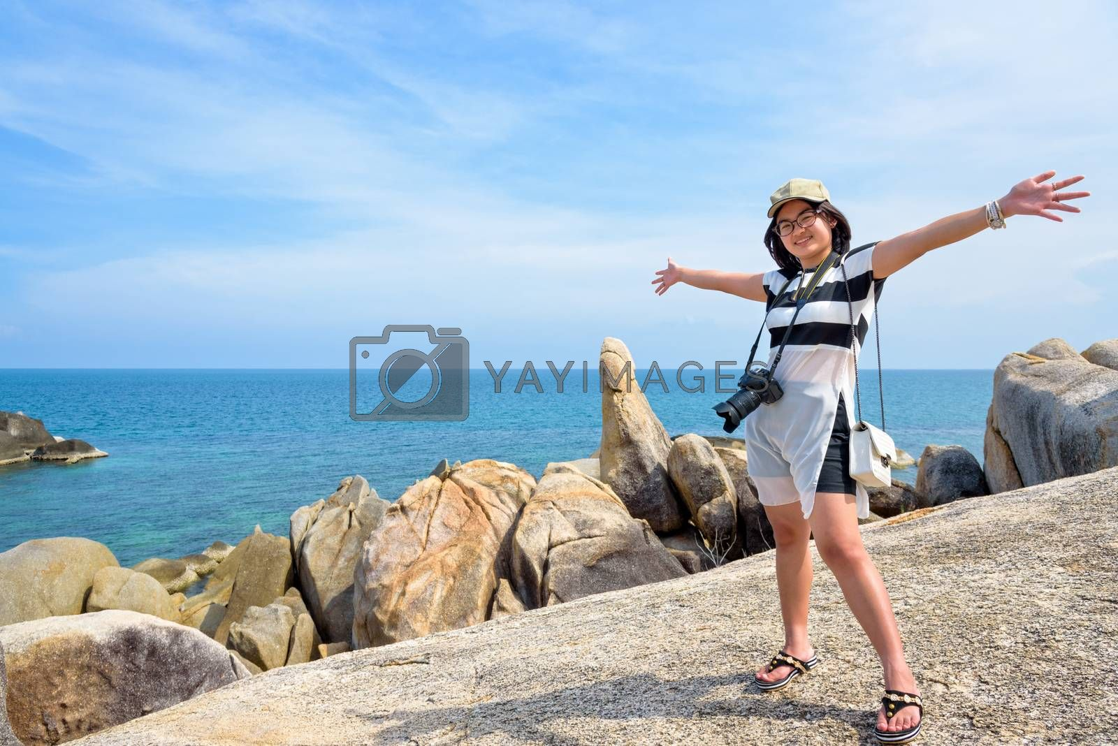 Young woman tourist is standing open arms and smile at Hin Ta Hin Yai and beautiful nature landscape of blue sea and sky during summer travel at Koh Samui island, Surat Thani, Thailand