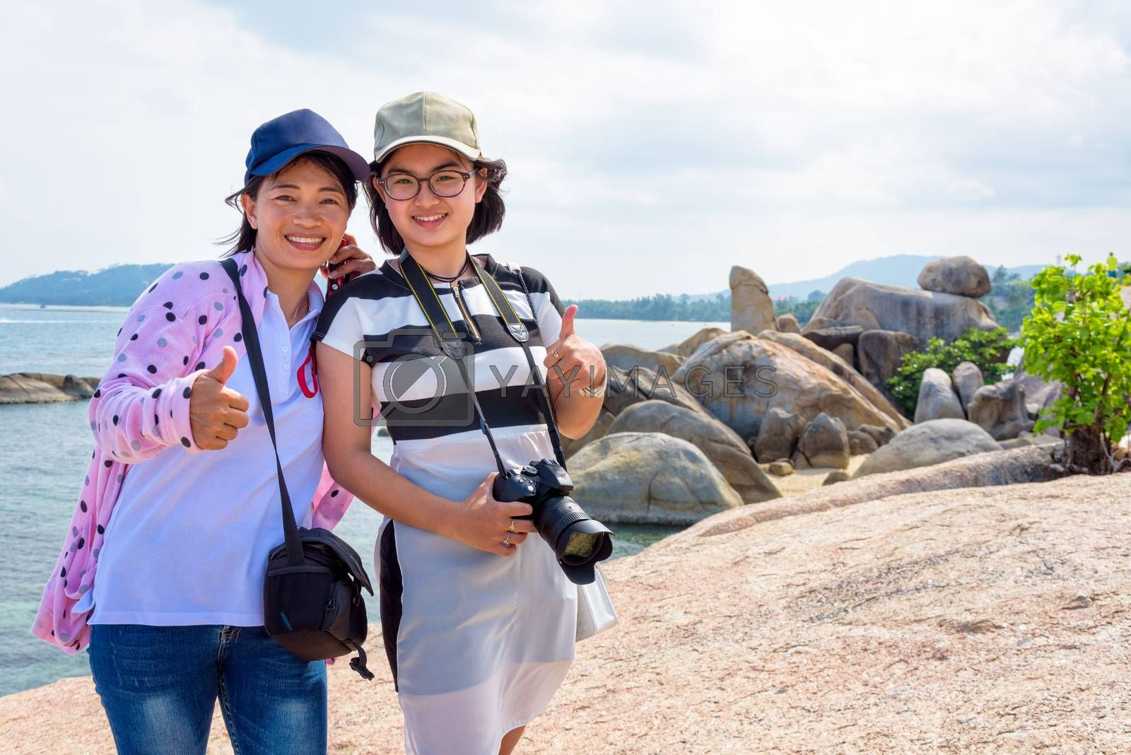 Mother and daughter standing thumb up and smiling happily at Hin Ta Hin Yai and beautiful nature landscape of blue sea and sky during summer travel at Koh Samui island, Surat Thani, Thailand