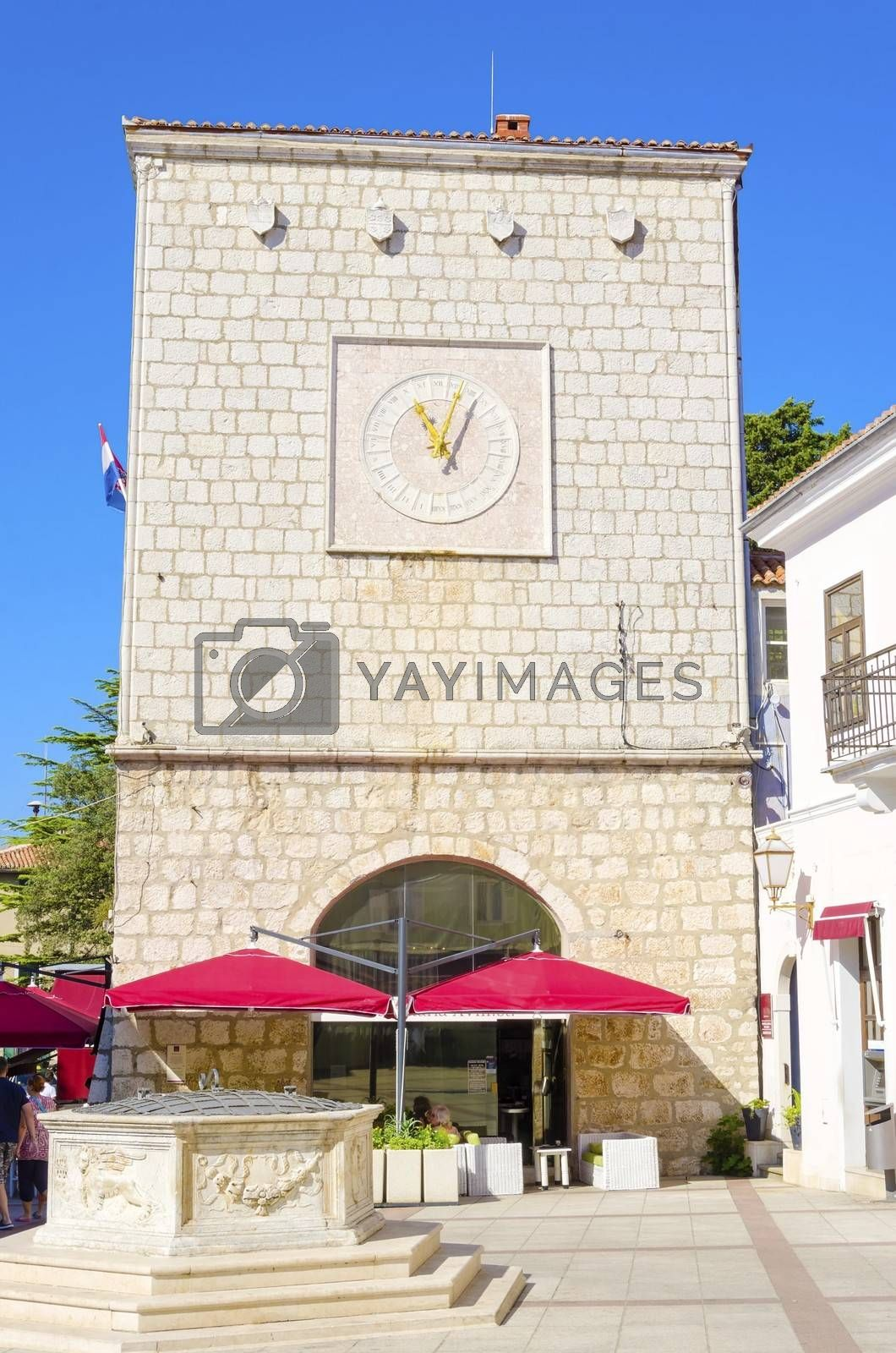 The Krk Town Council Hall clock at Vale Market place on island Krk, Croatia and the six-sided well. A rook medieval structure with a clock with latin numbers and yellow pointers.