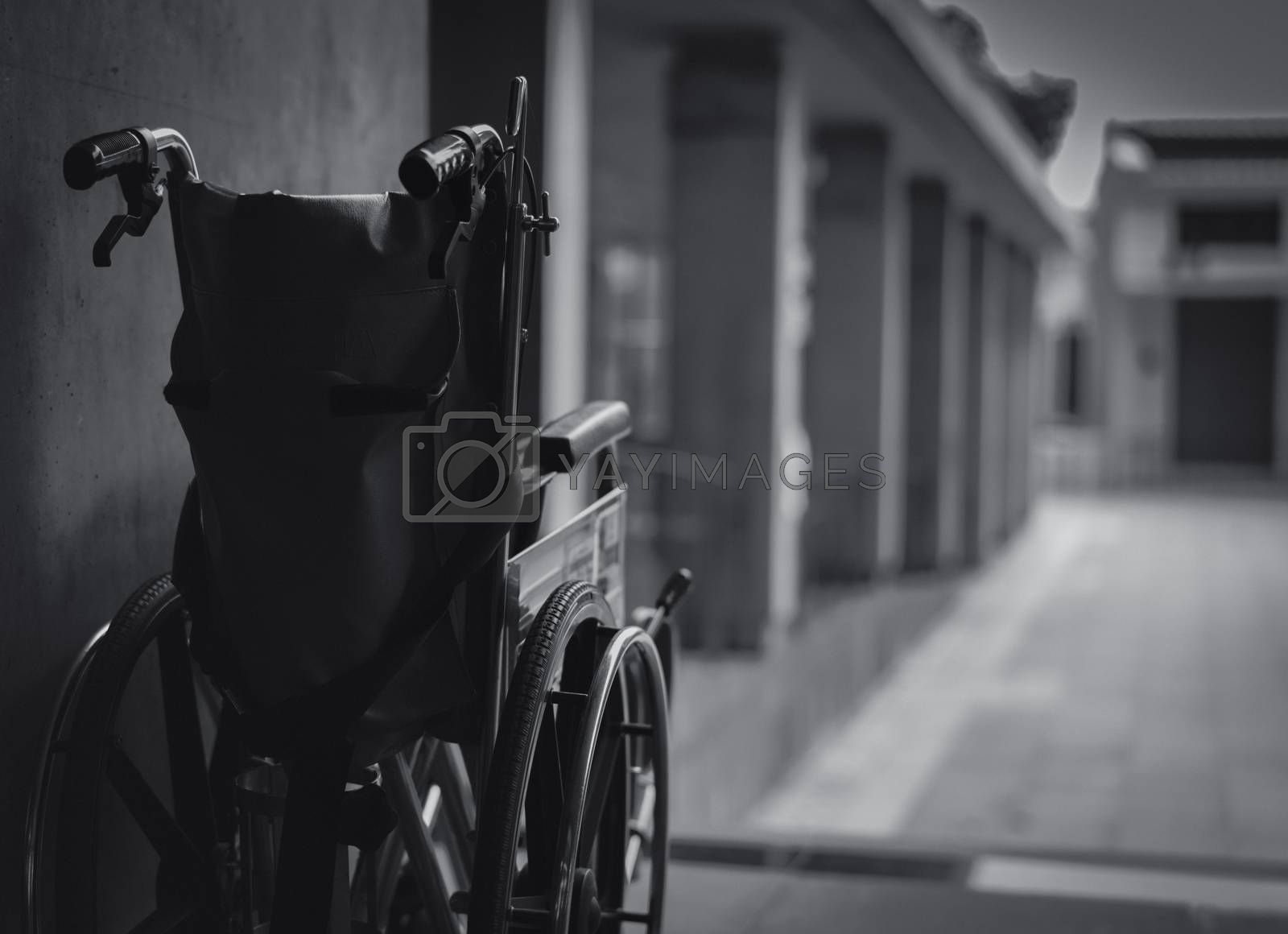 Wheelchair folded beside the wall. Sad news at the hospital concept. Depression with aging society. Lonely empty wheelchair. Medical equipment for service patient and assistant disabled elderly people