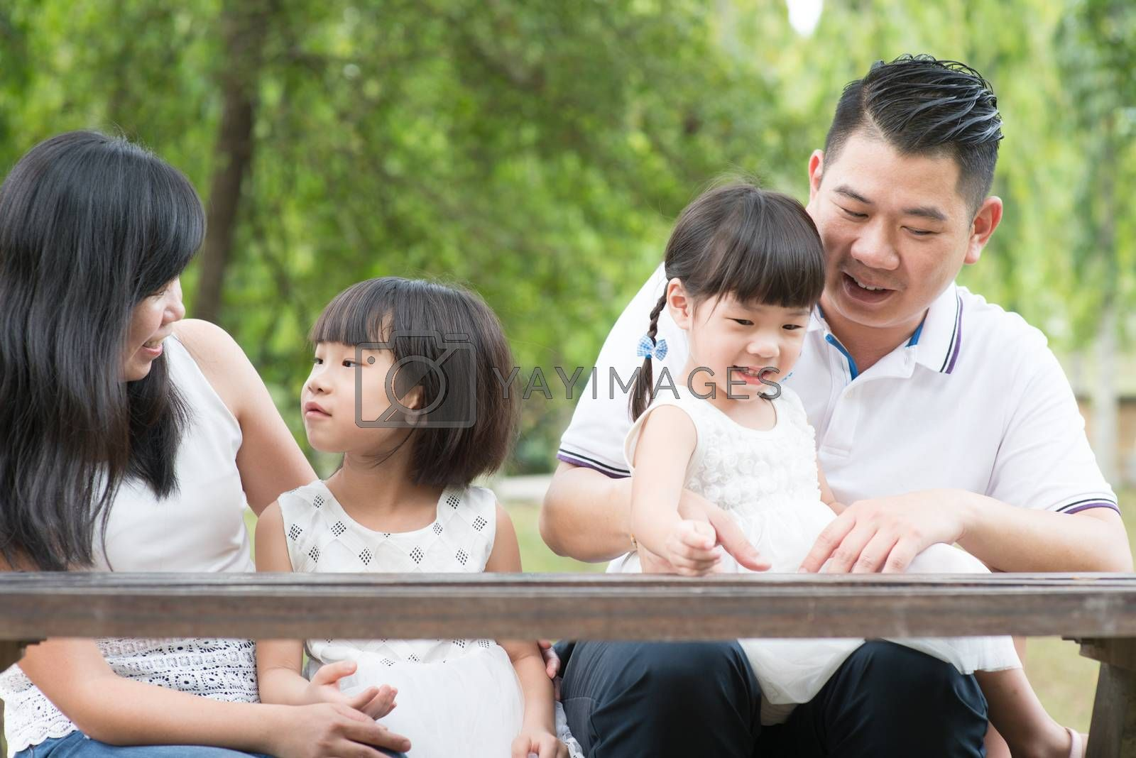 Asian family. Parents and children having fun at outdoor park. Empty space on wooden table.