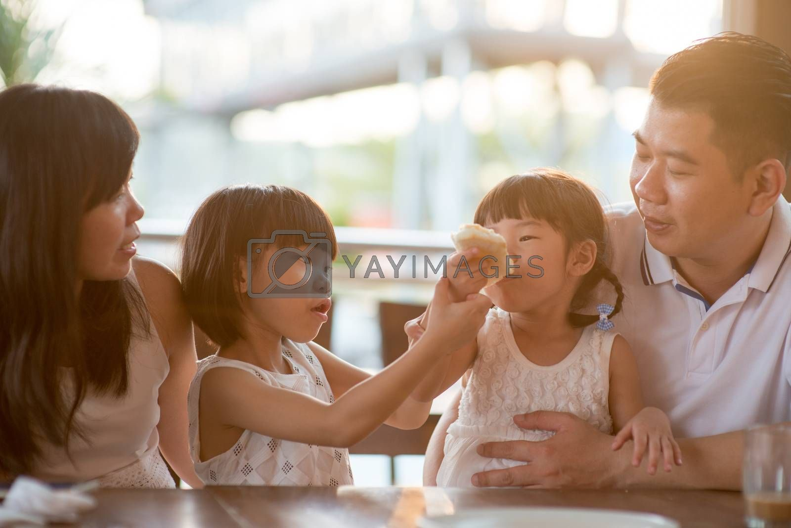 Adorable children eating and sharing butter toast at cafeteria. Asian family outdoor lifestyle with natural light.