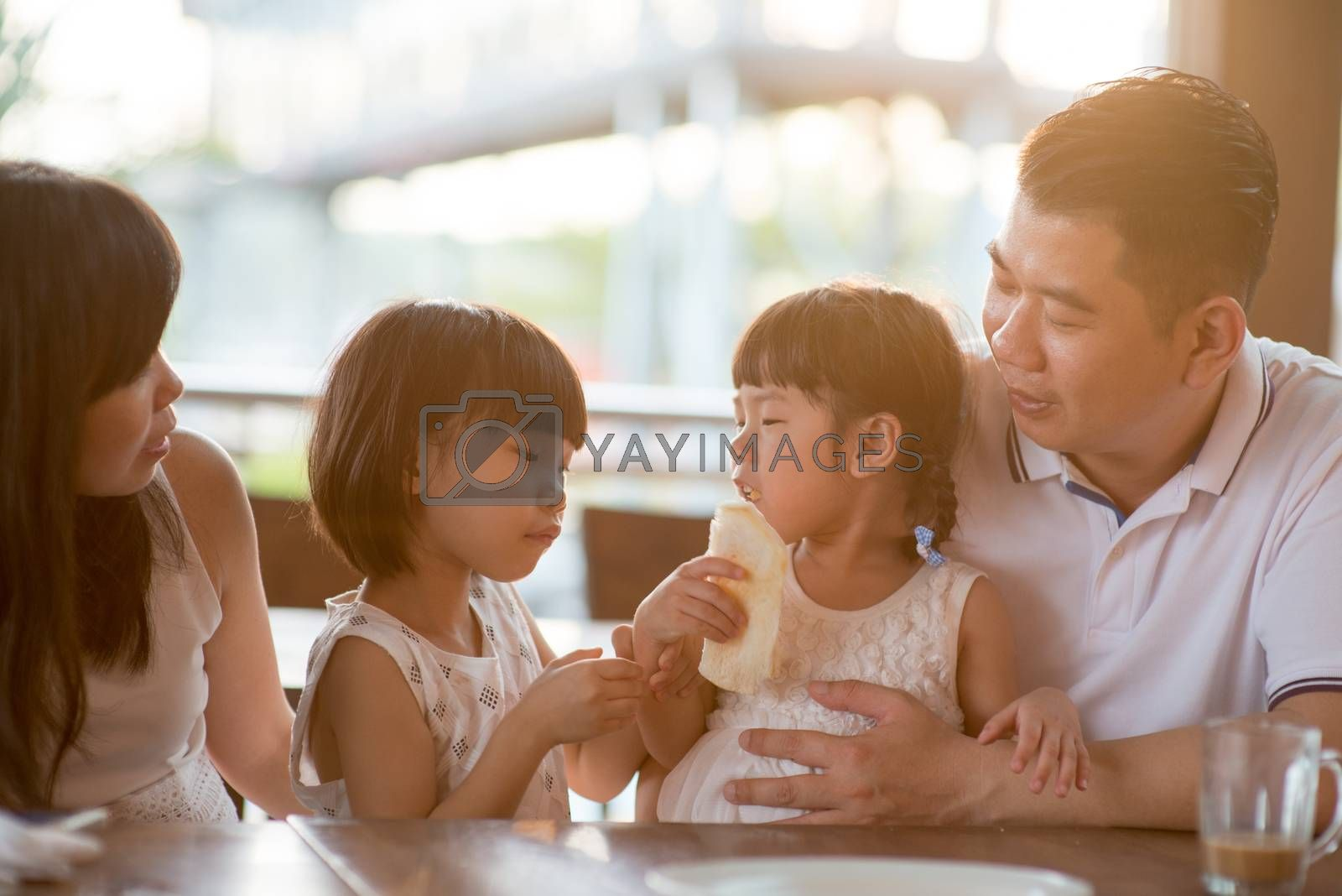 Cute children eating and sharing bread at cafeteria. Asian family outdoor lifestyle with natural light.