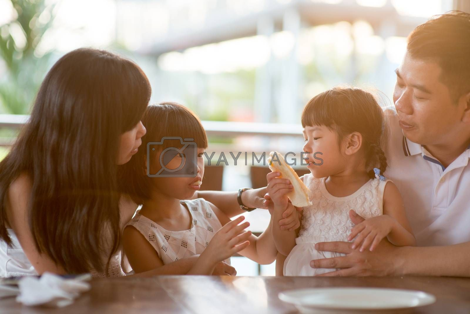 Happy children eating and sharing bread at cafeteria. Asian family outdoor lifestyle with natural light.