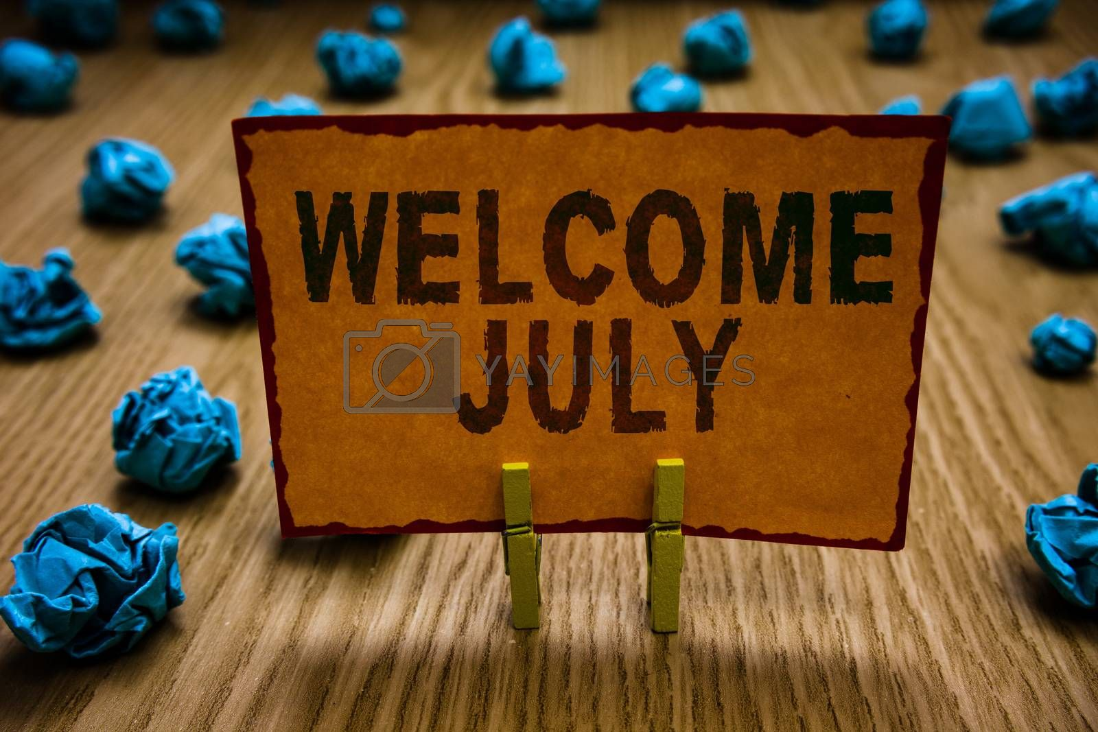 Royalty free image of Conceptual hand writing showing Welcome July. Business photo text Calendar Seventh Month 31days Third Quarter New Season Clothespins holding orange paper note crumpled papers mistake. by artursz