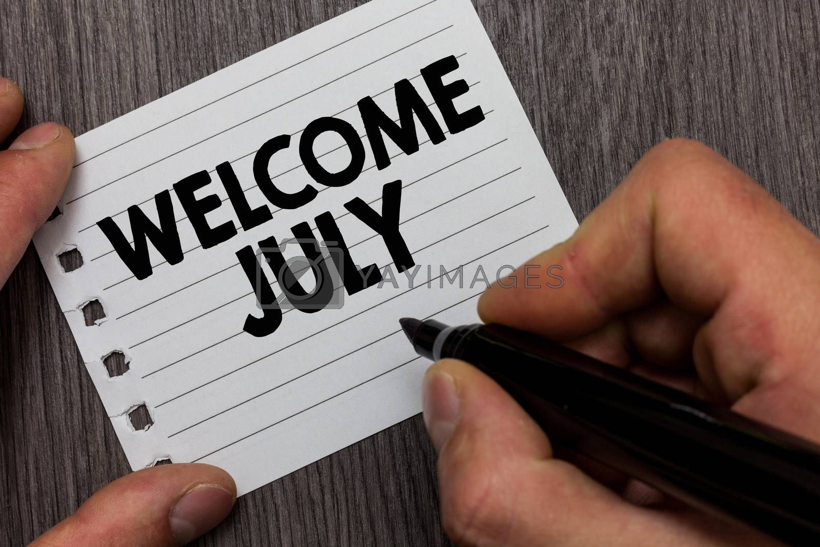 Royalty free image of Conceptual hand writing showing Welcome July. Business photo showcasing Calendar Seventh Month 31days Third Quarter New Season Man holding marker notebook page Wooden background. by artursz